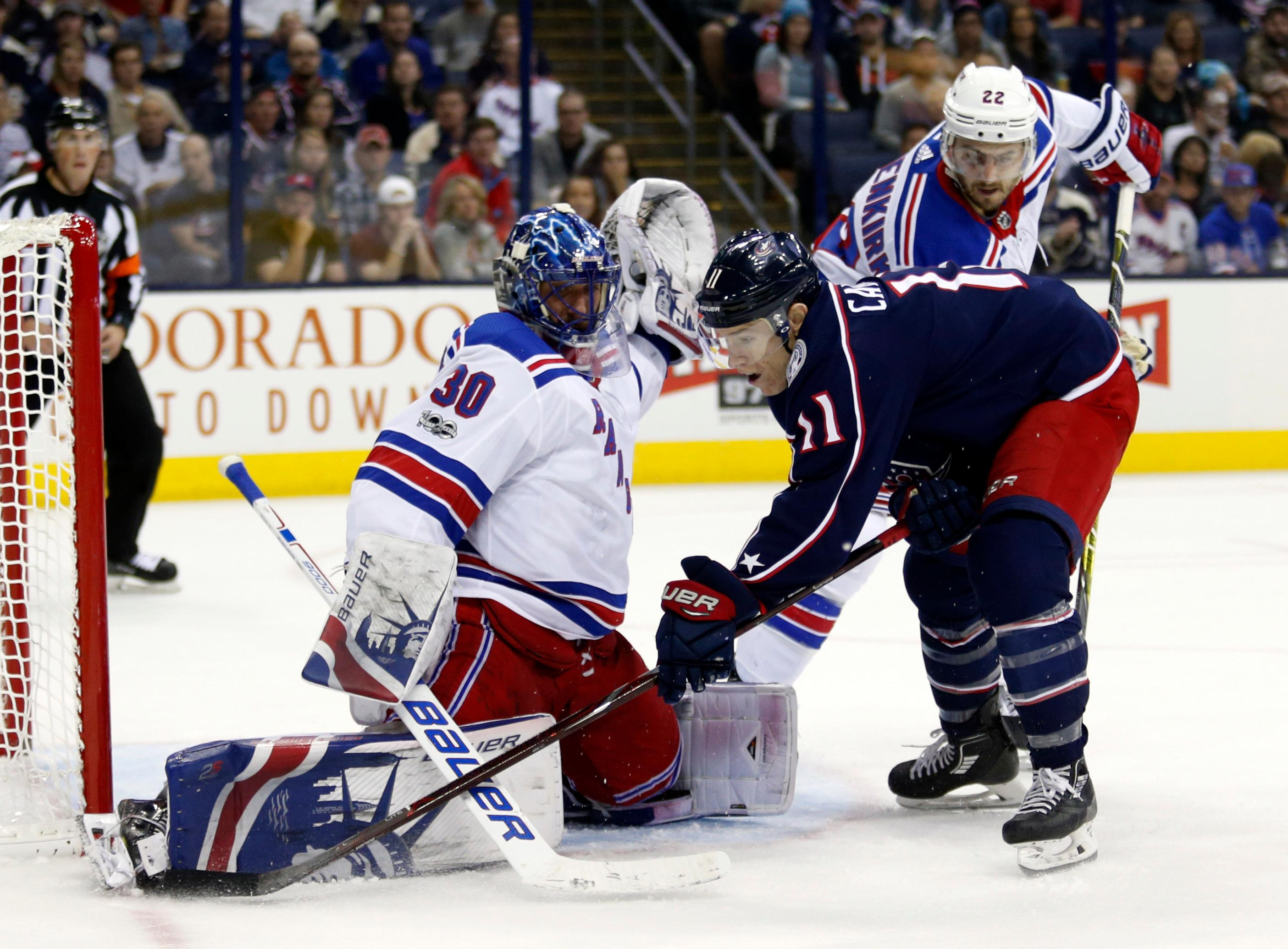 New York Rangers goalie Henrik Lundqvist, left, of Sweden, stops a shot by Columbus Blue Jackets forward Matt Calvert as Rangers defenseman Kevin Shattenkirk defends during the second period of an NHL hockey game in Columbus, Ohio, Friday, Oct. 13, 2017. (AP Photo/Paul Vernon)