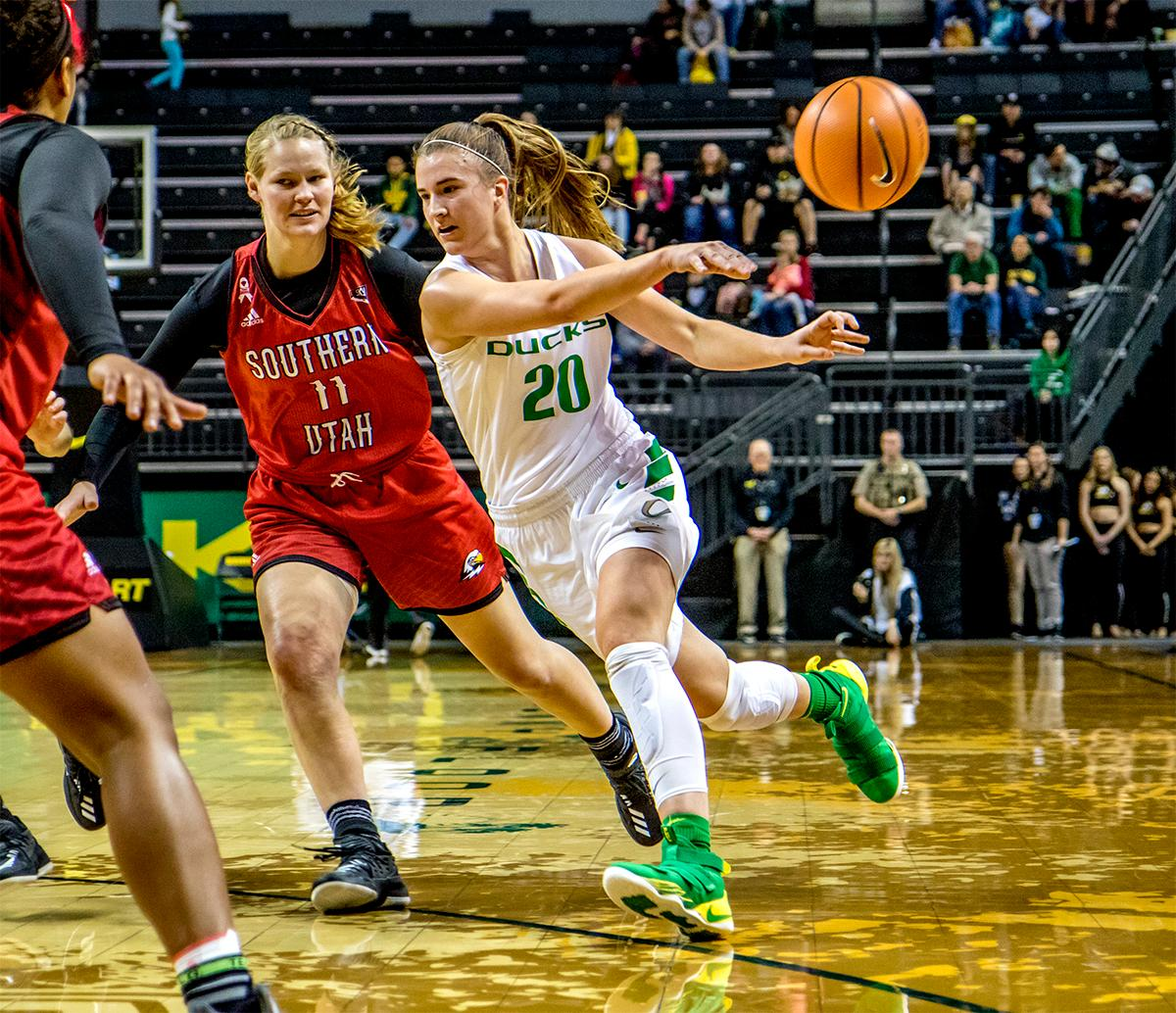The Duck's Sabrina Ionescu (#20) tosses the ball aside to a teammate. The University of Oregon Ducks women basketball team defeated the Southern Utah Thunderbirds 98-38 in Matthew Knight Arena Saturday afternoon. The Ducks had four players in double-digits: Ruthy Hebard with 13; Mallory McGwire with 10; Lexi Bando with 17 which included four three-pointers; and Sabrina Ionescu with 16 points. The Ducks overwhelmed the Thunderbirds, shooting 50% in field goals to South Utah's 26.8%, 53.8% in three-pointers to 12.5%, and 85.7% in free throws to 50%. The Ducks, with an overall record of 8-1, and coming into this game ranked 9th, will play their next home game against Ole Miss on December 17. Photo by August Frank, Oregon News Lab