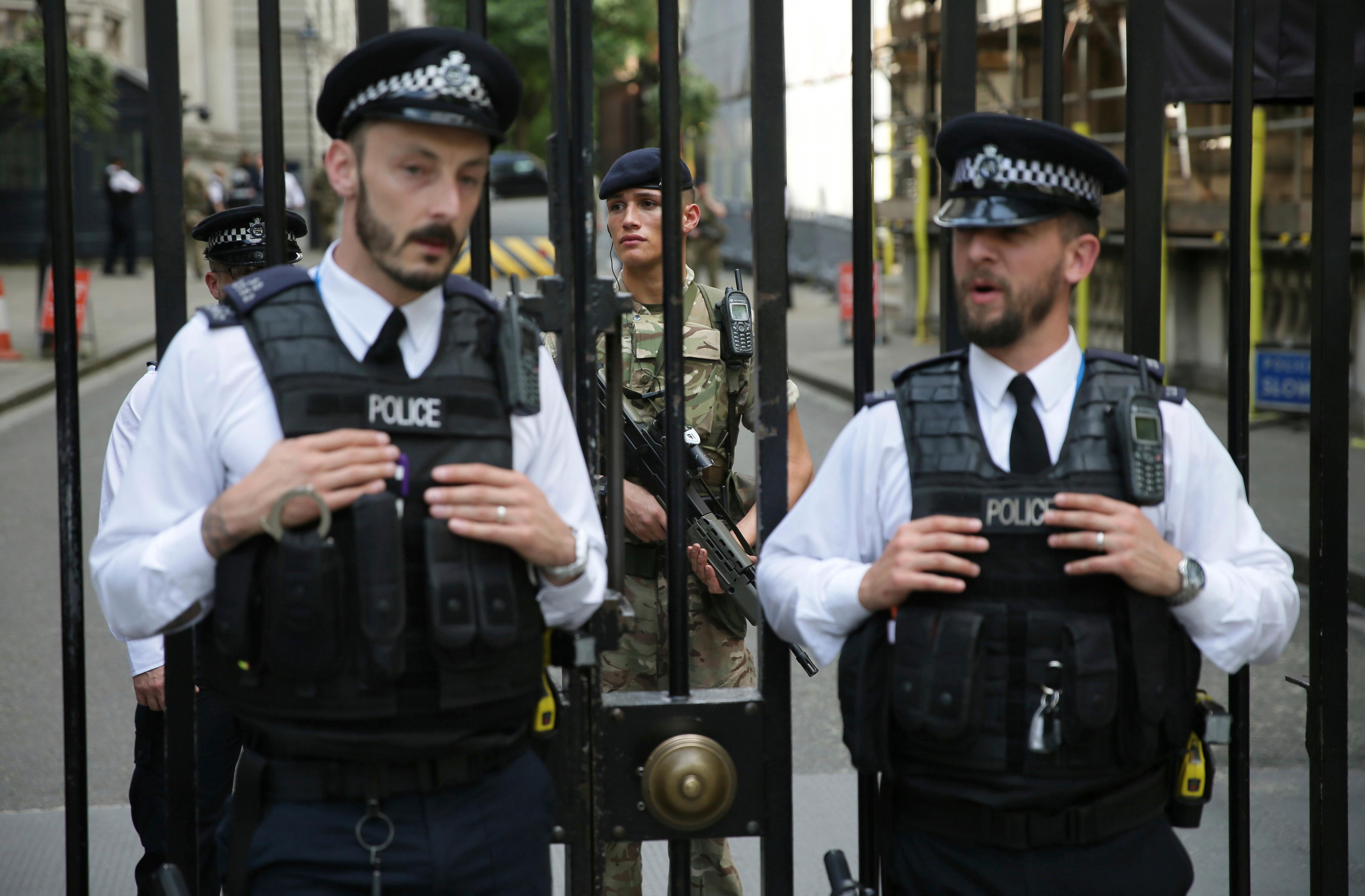 A soldier joins armed police officers guarding Downing Street in London, Wednesday May 24, 2017. Britons will find armed troops at vital locations Wednesday after the official threat level was raised to its highest point following a suicide bombing that killed 22, as new details emerged about the bomber. (AP Photo/Tim Ireland)