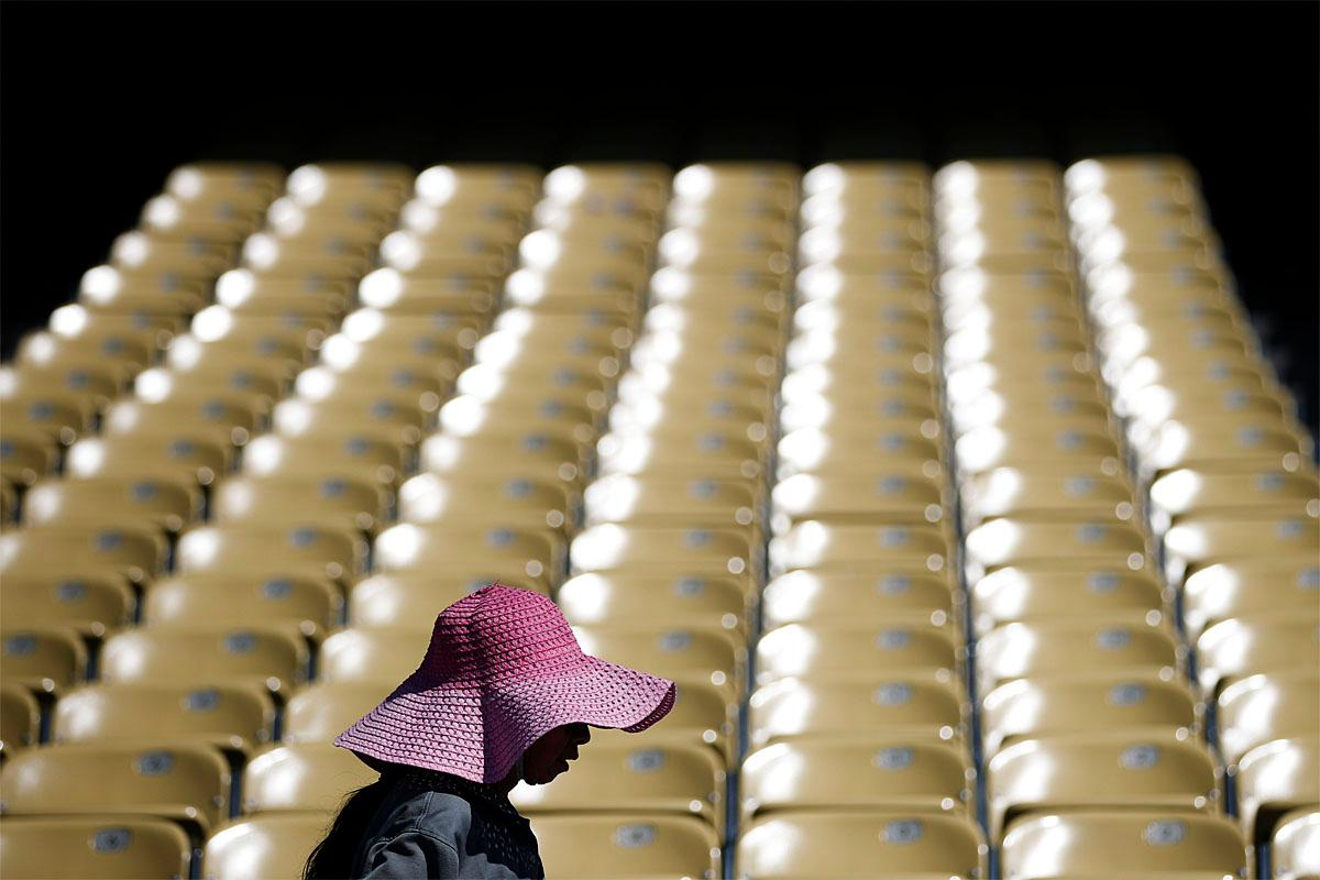 A worker wears a large hat, wet with water, to shield from the sun while cleaning the seats at Dodger Stadium, Monday, June 19, 2017, in Los Angeles. A punishing heat wave has arrived in the Southwestern U.S. and brought temperatures that will approach 120 degrees in Arizona. (AP Photo/Jae C. Hong)