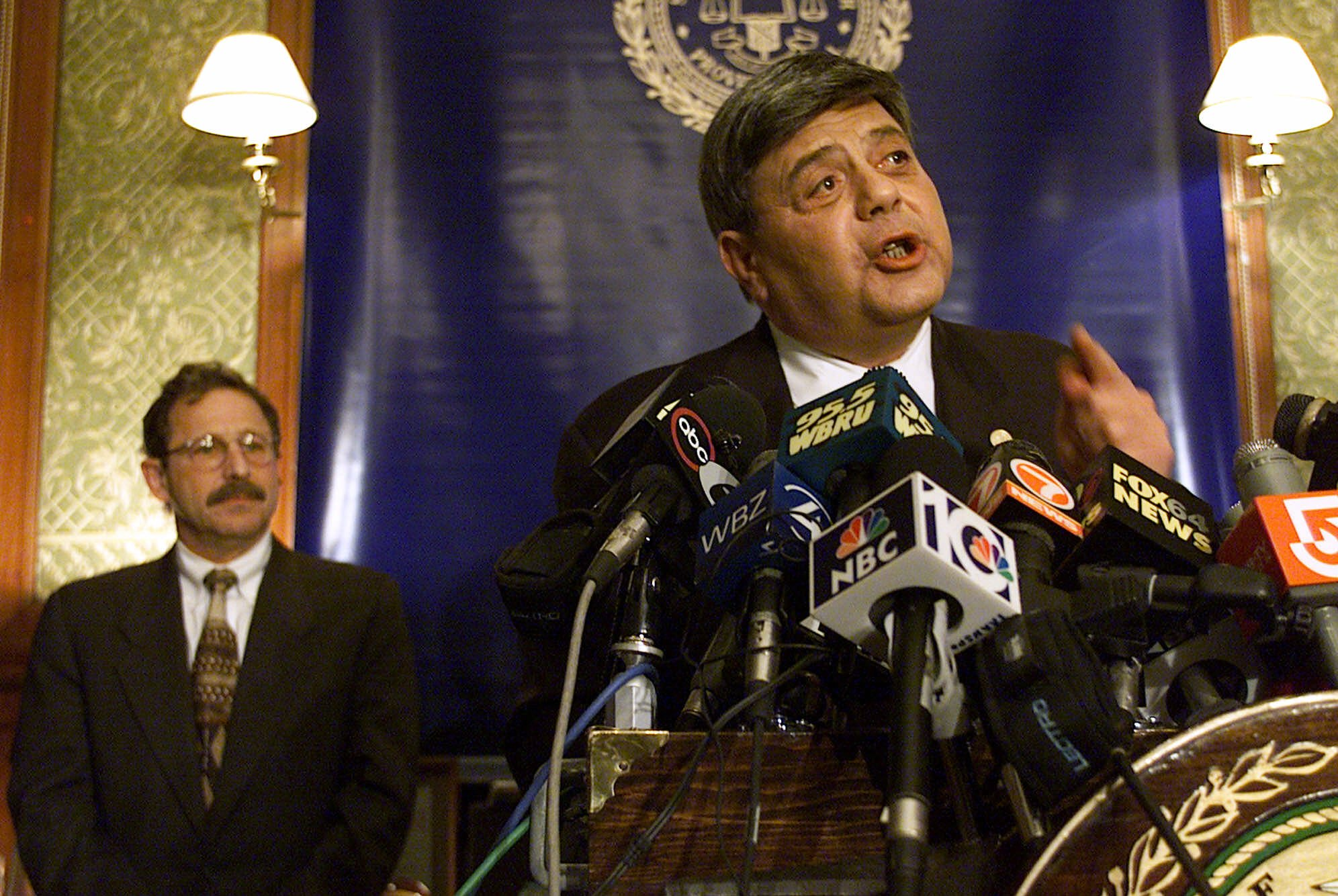 "Providence, R.I., Mayor Vincent Cianci Jr. speaks to members of the media as his attorney Richard Eggbert, left, stands behind him in his City Hall office, Monday, April 2, 2001. Cianci was indicted by a federal grand jury Monday on charges of racketeering and claims of taking bribes in exchange for city contracts and police promotions.  Cianci denied any wrongdoing, calling the details in the massive indictment ""nothing but lies."" (AP Photo/Victoria Arocho)"