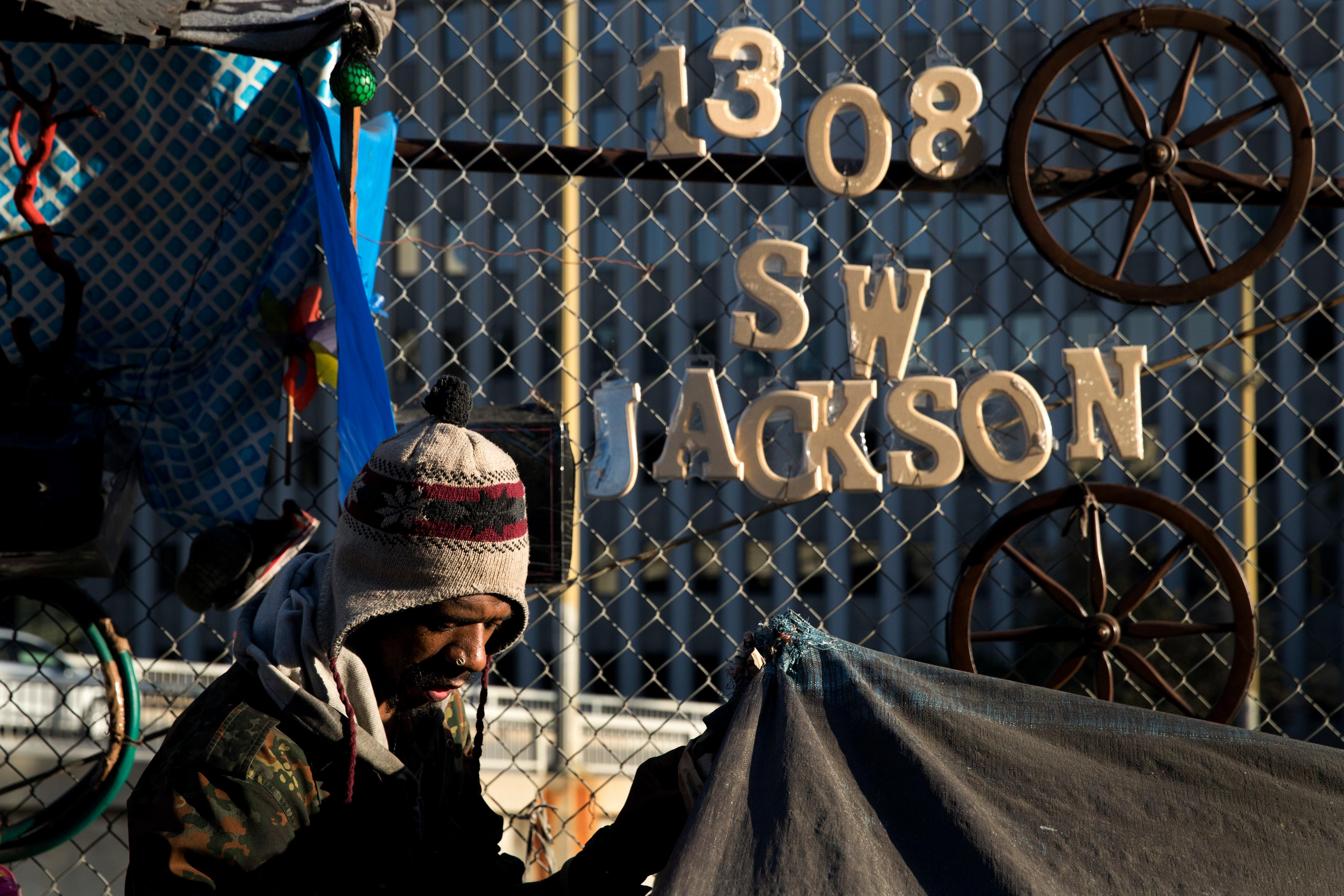 "Thaddeus Bell, 50, who is homeless, sits outside his tent with the street address of his childhood home in Oklahoma hanging on a fence Monday, Dec. 4, 2017, in Los Angeles. ""I might be homeless but I'm human just like everybody else,"" said Bell. ""I deserve a real house like any other person."" The U.S. Department on Housing and Urban Development release of the 2017 homeless numbers are expected to show a dramatic increase in the number of people lacking shelter along the West Coast. (AP Photo/Jae C. Hong)"