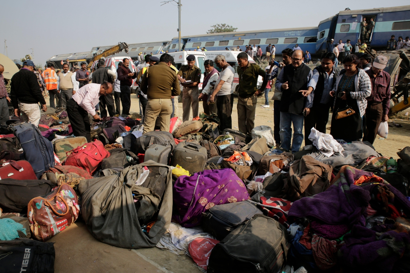 People stand near belongings of passengers after 14 coaches of an overnight passenger train rolled off the track near Pukhrayan village Kanpur Dehat district, Uttar Pradesh state, India, Sunday, Nov. 20, 2016. Dozens were killed and dozens more were injured in the accident. (AP Photo/Rajesh Kumar Singh)