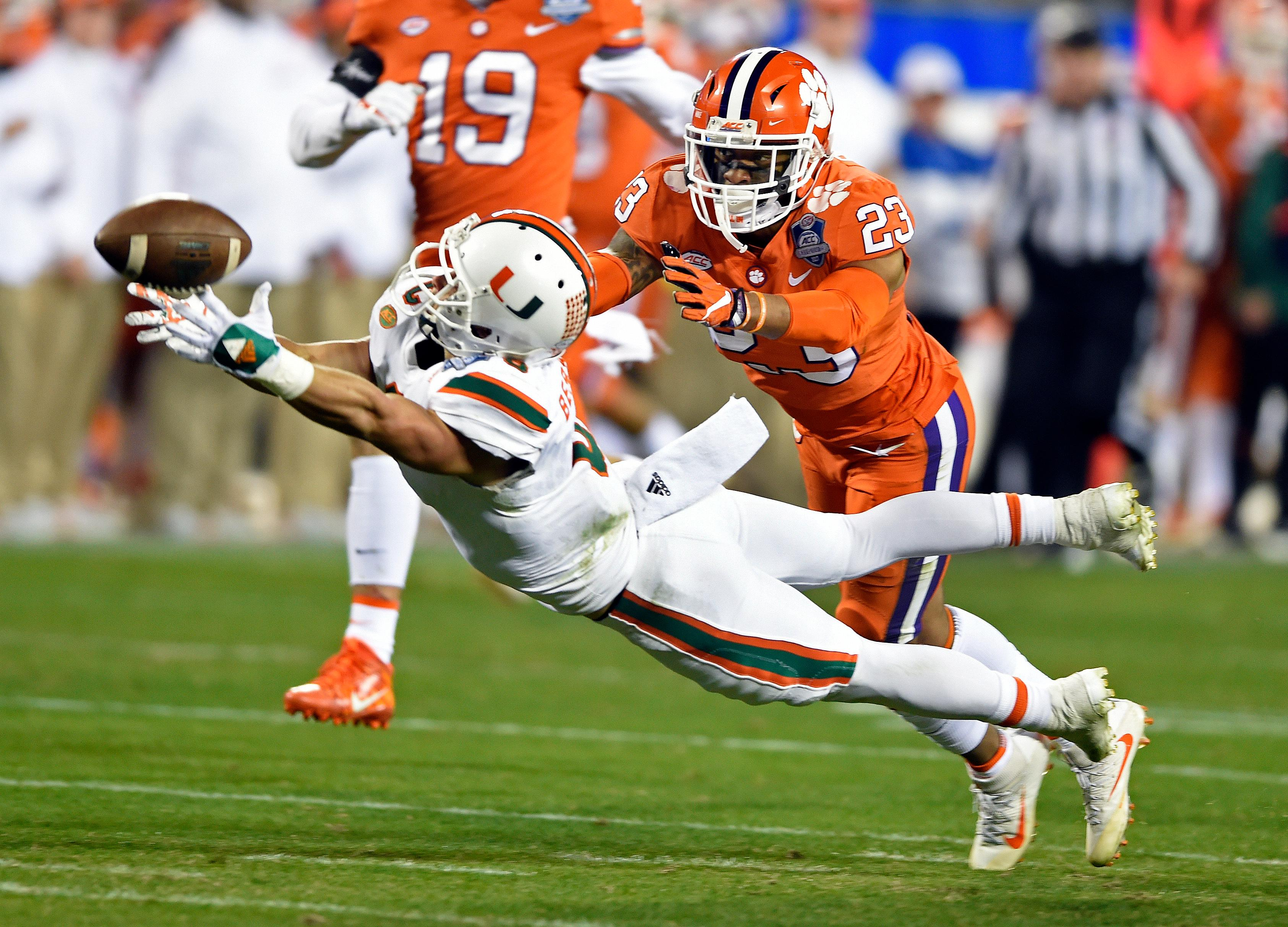 Miami's Braxton Berrios (8) misses a catch as Clemson's Van Smith (23) defends during the second half of the Atlantic Coast Conference championship NCAA college football game in Charlotte, N.C., Saturday, Dec. 2, 2017. (AP Photo/Mike McCarn)