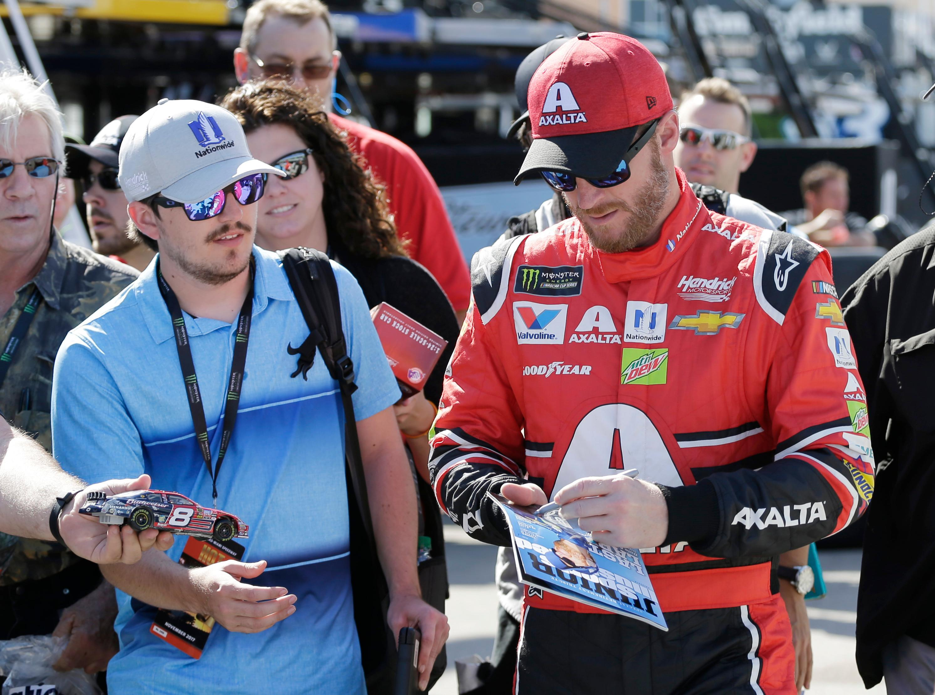 Dale Earnhardt Jr., right, gives autographs in the garage area during practice for Sunday's NASCAR Cup Series auto race at Homestead-Miami Speedway in Homestead, Fla., Friday, Nov. 17, 2017. (AP Photo/Terry Renna)