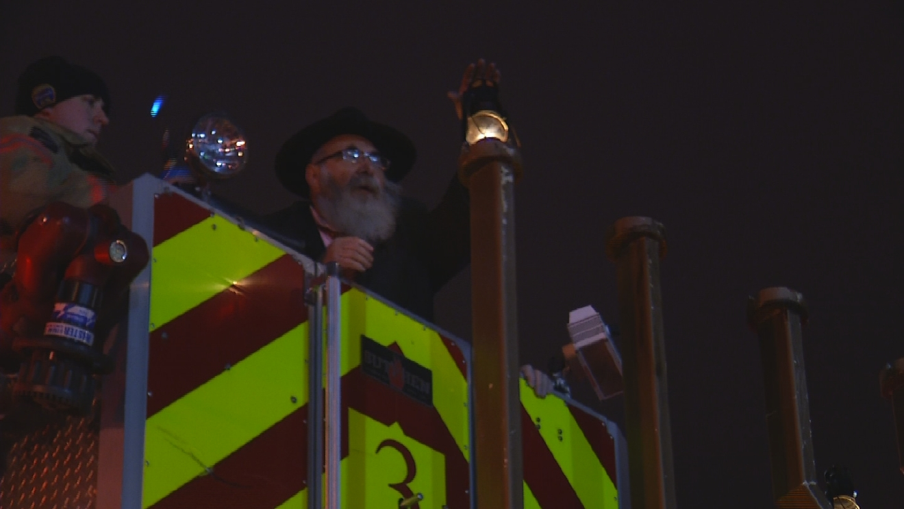 The Syracuse Fire Department lifting Rabbi Yaakov Rapoport into the air to light the first branch of the menorah.