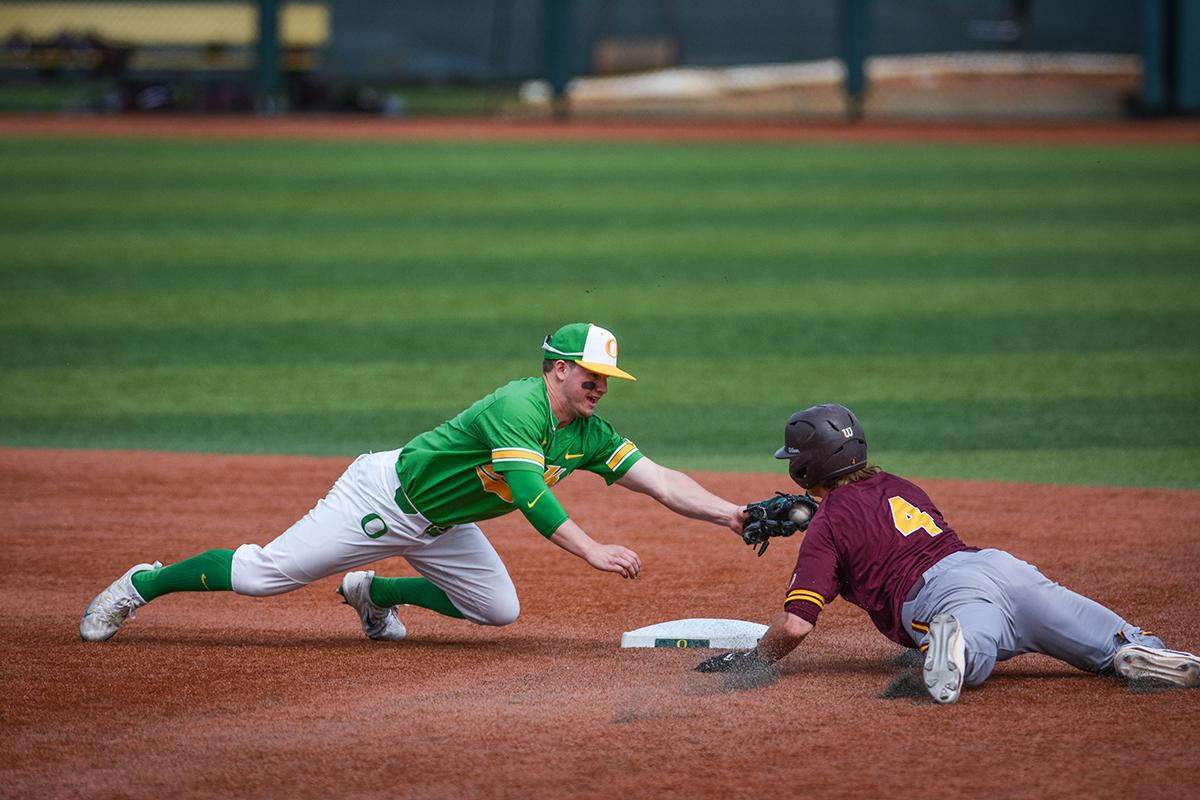 Ducks infielder Morgan McCullough (#9) dives to tag Sun Devils Andrew Snow (#4) who slides into second base. Despite a late comeback, the Ducks fall to Arizona State Sun Devils 4-3 in the second game of a three-game series. Photo by Jacob Smith, Oregon News Lab