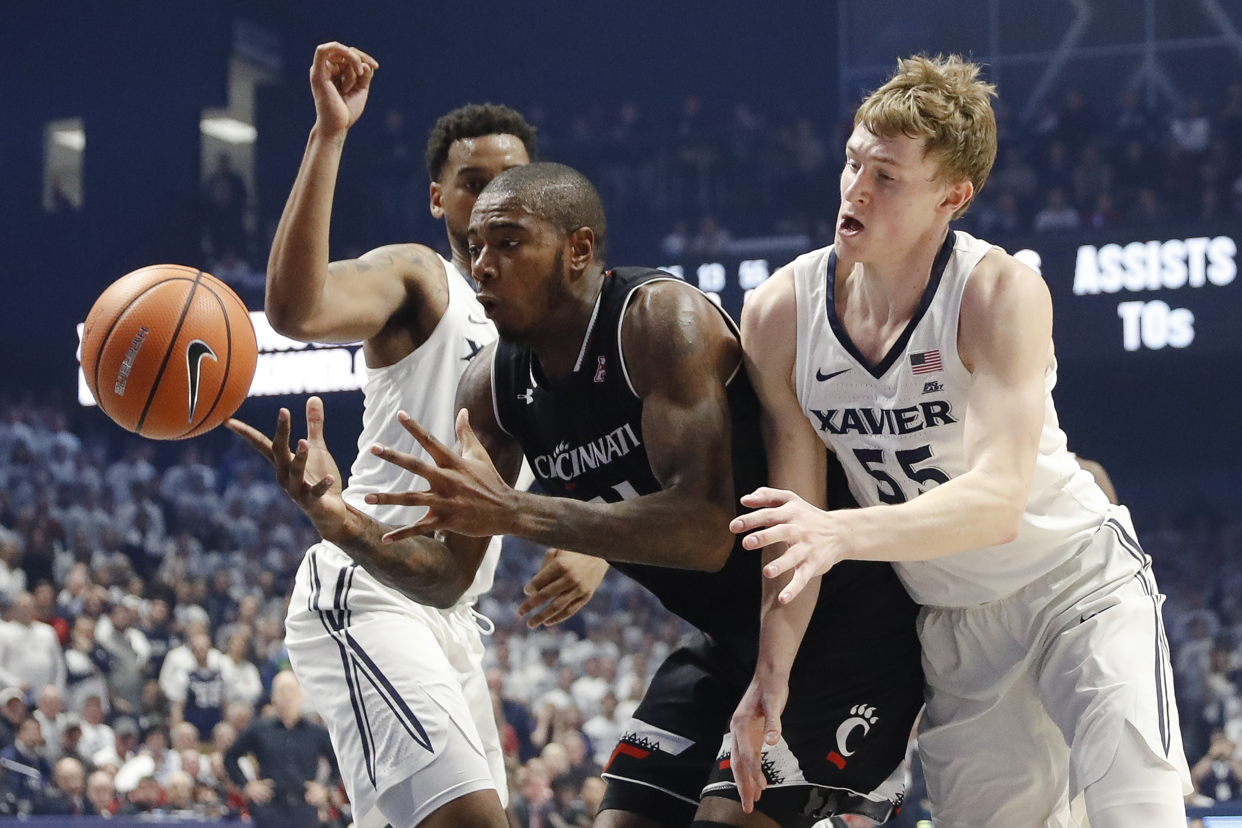 Cincinnati's Gary Clark, center, and Xavier's J.P. Macura (55) battle for a rebound in the first half of an NCAA college basketball game, Saturday, Dec. 2, 2017, in Cincinnati. (AP Photo/John Minchillo)