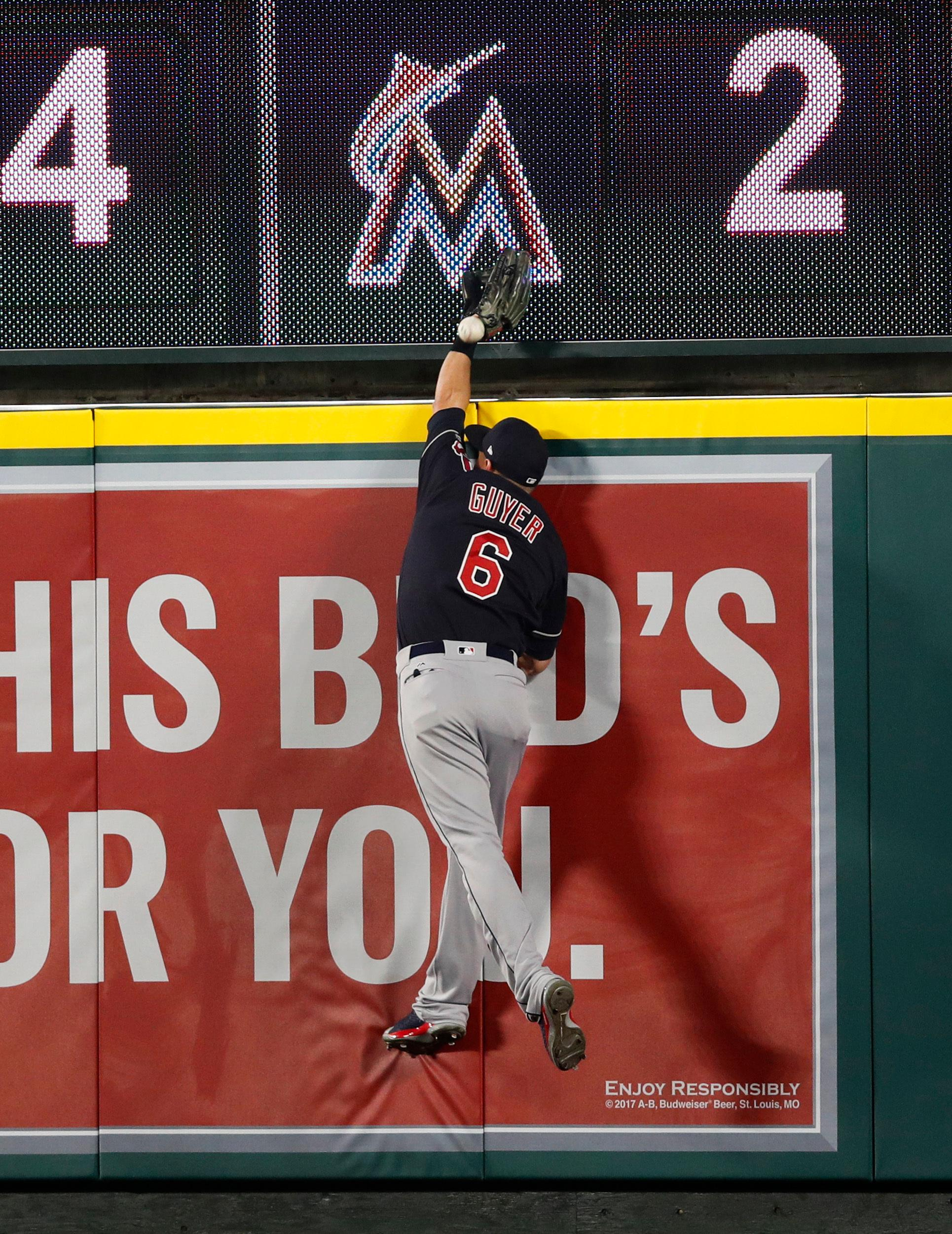 Cleveland Indians' Brandon Guyer can't catch a ball hit by Los Angeles Angels' Rene Rivera during the eighth inning of a baseball game, Tuesday, April 3, 2018, in Anaheim, Calif. The hit was ruled a home run after a video review. (AP Photo/Jae C. Hong)
