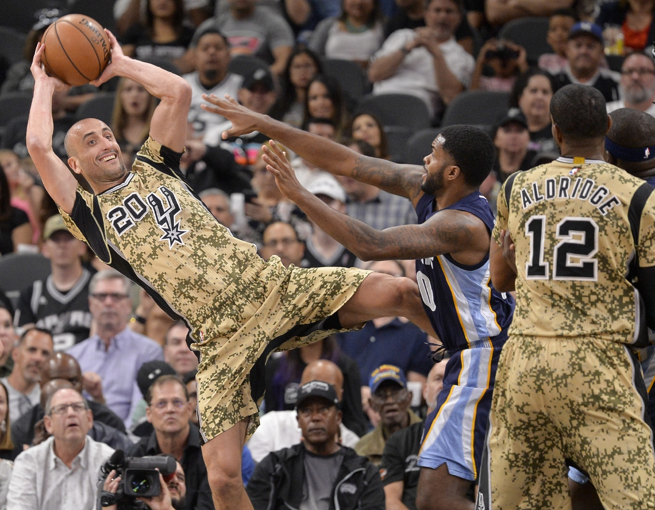 San Antonio Spurs guard Manu Ginobili (20), of Argentina, looks to pass to forward LaMarcus Aldridge (12) as he is defended by Memphis Grizzlies forward Troy Daniels (30) during the first half of an NBA basketball game, Thursday, March 23, 2017, in San Antonio. (AP Photo/Darren Abate)