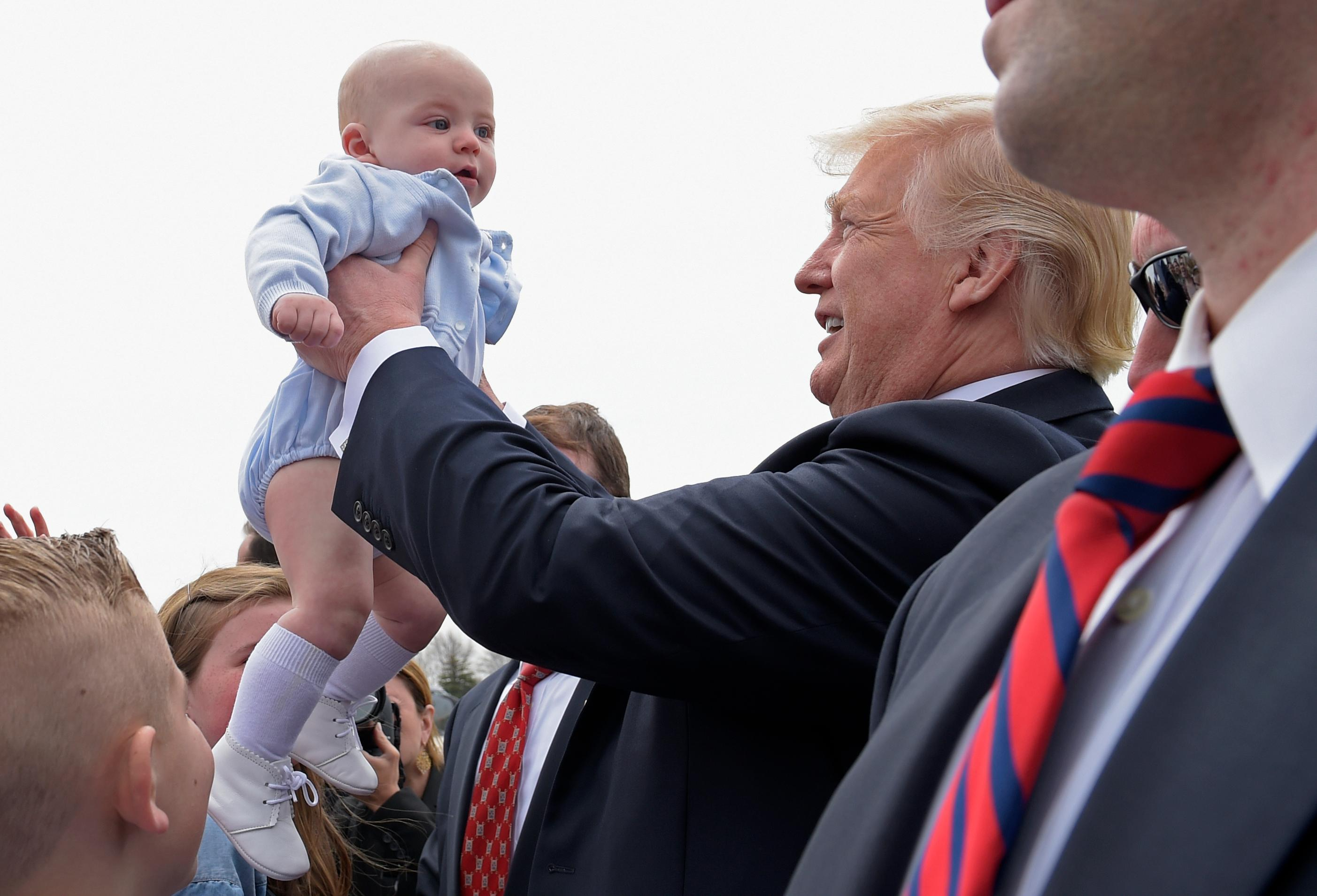 President Donald Trump picks up a baby as he greets people after arriving on Air Force One at General Mitchell International Airport in Milwaukee, Tuesday, April 18, 2017. Trump is heading to Kenosha, Wis., to visit the headquarters of tool manufacturer Snap-on Inc., and sign an executive order that seeks to make changes to a visa program that brings in high-skilled workers. (AP Photo/Susan Walsh)
