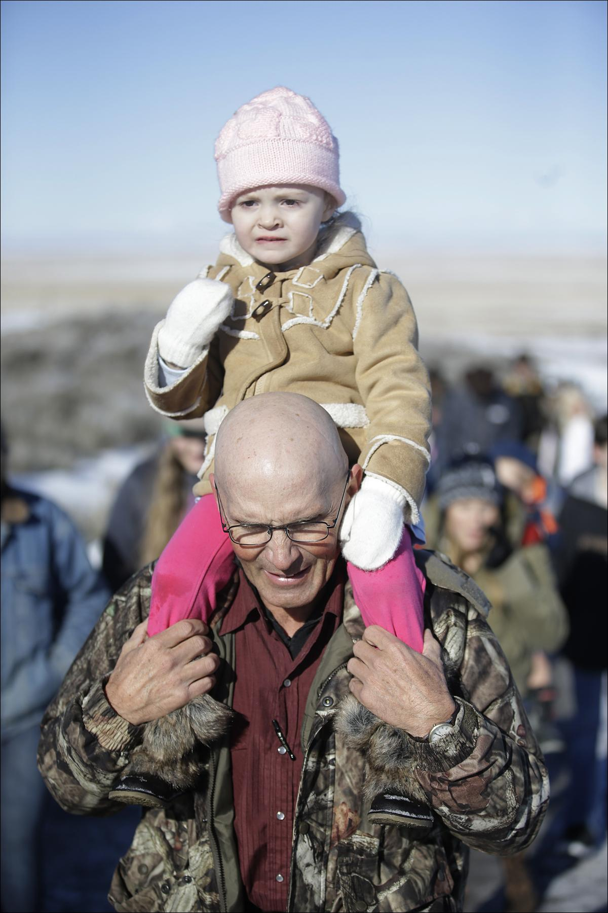 LaVoy Finicum, a rancher from Arizona,  carries his granddaughter Payton, 3, before a news conference at Malheur National Wildlife Refuge Friday, Jan. 8, 2016, near Burns, Ore. Ammon Bundy, the leader of a small, armed group occupying a national wildlife refuge in Oregon says the activists have no immediate plans to leave. Bundy spoke to reporters Friday, a day after meeting with a local sheriff who asked the group to go. (AP Photo/Rick Bowmer)
