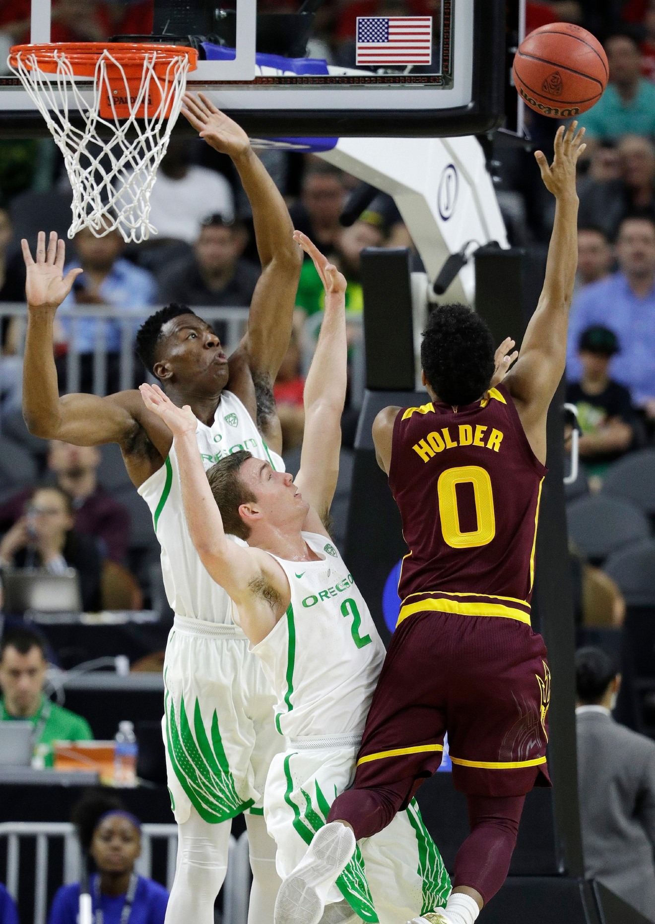 Oregon's Kavell Bigby-Williams, left, and Casey Benson, center, try to block a shot by Arizona State's Tra Holder during the first half of an NCAA college basketball game in the first round of the Pac-12 men's tournament Thursday, March 9, 2017, in Las Vegas. (AP Photo/John Locher)