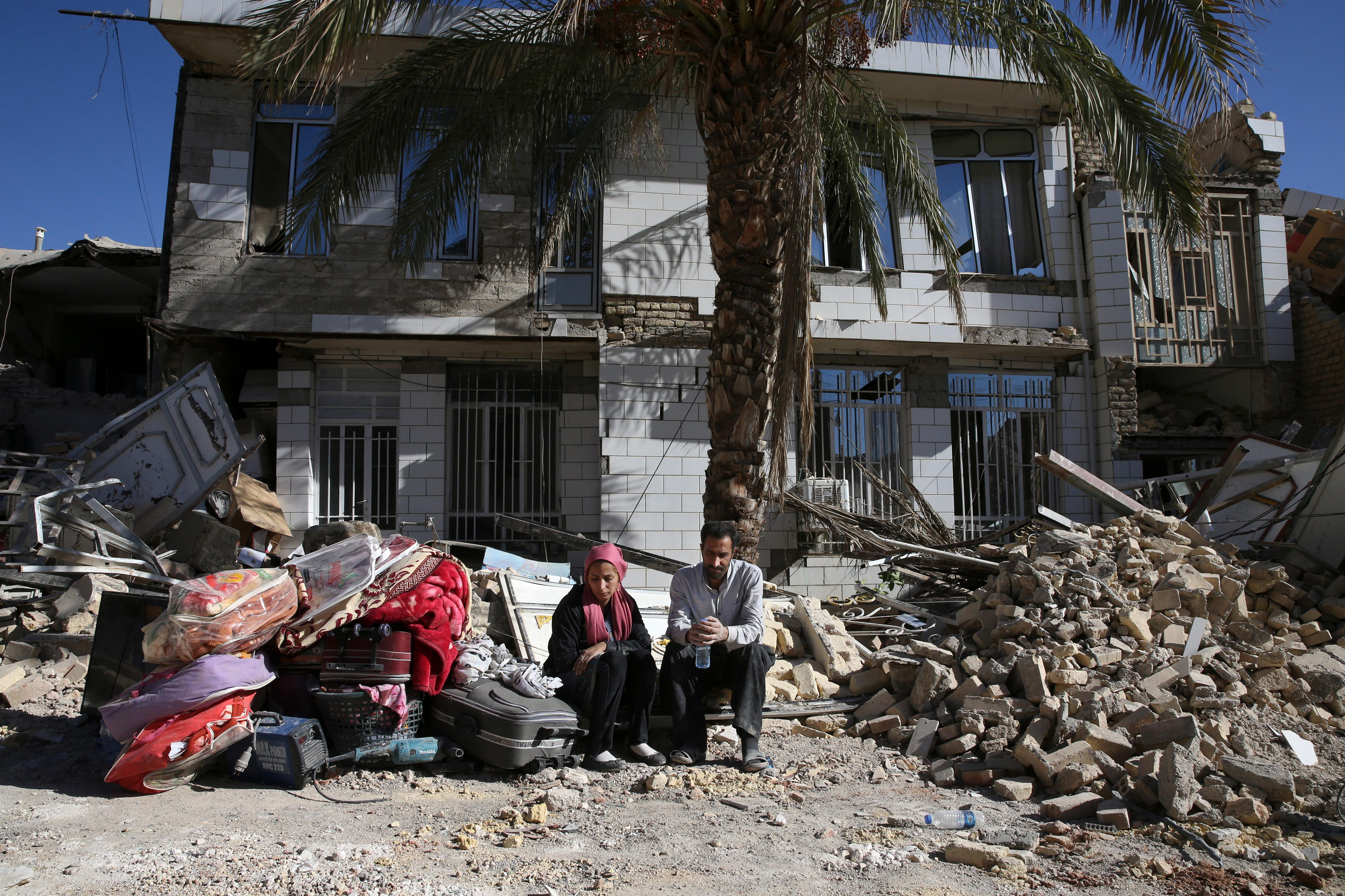 Survivors sit in front of a destroyed house on the earthquake site in Sarpol-e-Zahab in western Iran, Tuesday, Nov. 14, 2017. Rescuers are digging through the debris of buildings felled by the Sunday earthquake in the border region of Iran and Iraq. (AP Photo/Vahid Salemi)