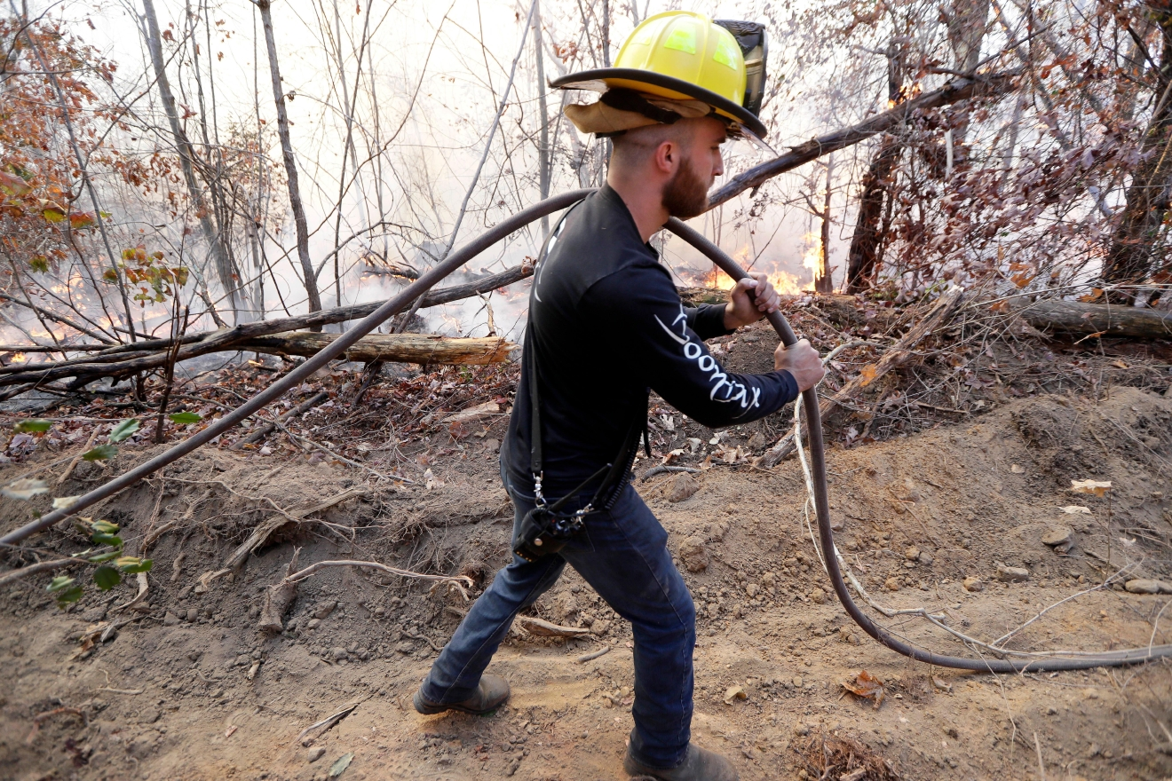 Lieutenant Jesse Mooney, of the Flat Top Mountain Volunteer Fire Department, carries a hose as firefighters battle a wildfire Thursday, Nov. 10, 2016, in Soddy-Daisy, Tenn. Federal authorities say warmer-than-average temperatures and no rainfall are deepening a drought that's sparking forest fires across the Southeastern U.S. (AP Photo/Mark Humphrey)