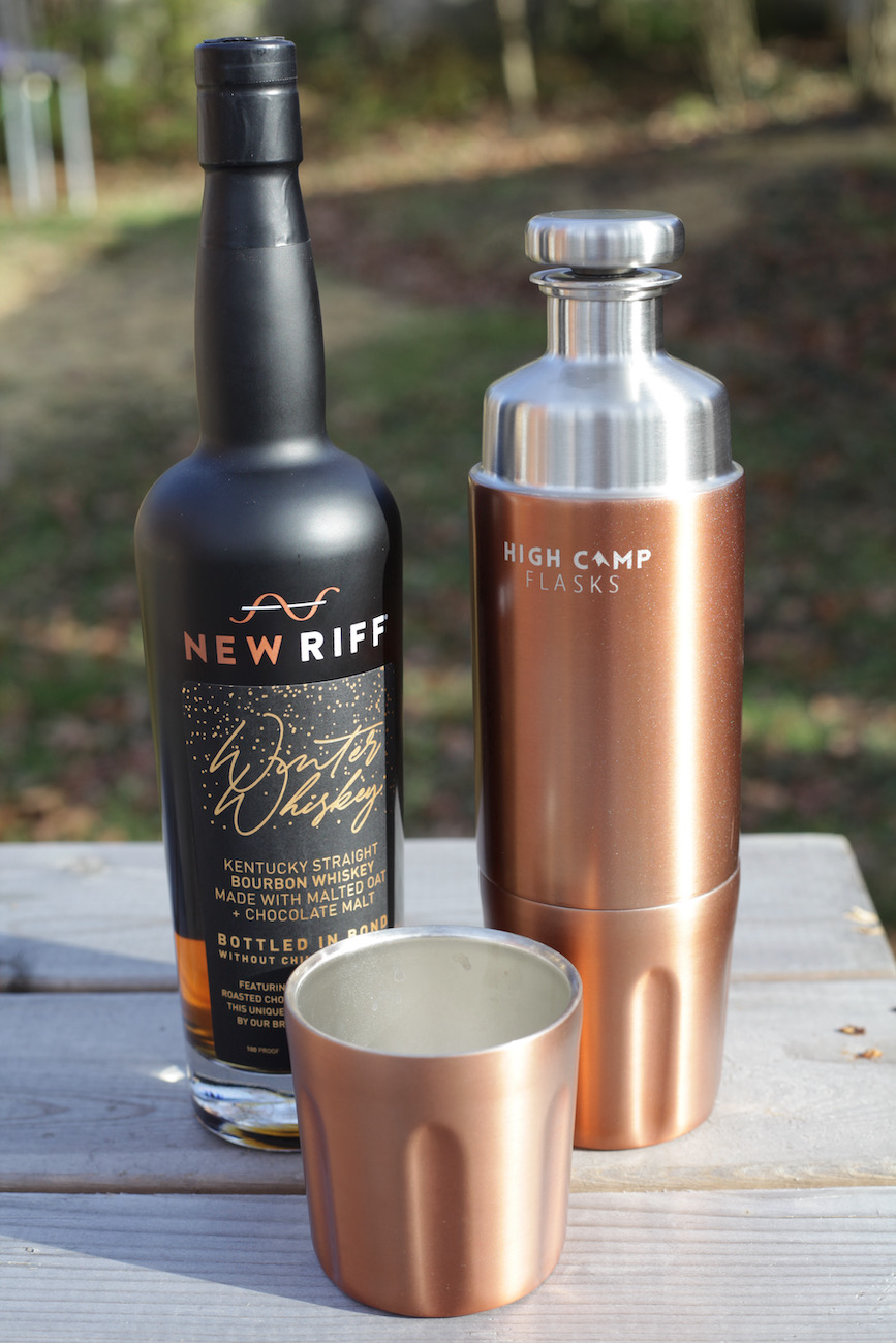 "<p>Class up your campsite or cabin with this stylist flask that carries 750ml of your favorite wine or spirit. The High Camp Flask—Firelight 750 Flask comes with two detachable tumblers that attach to the flask using a magnetic lock system. It pairs well with New Riff's latest Winter Whiskey. The Kentucky Straight Bourbon Whiskey made with malted oat and chocolate malt that's reminiscent of a chocolate oatmeal stout. It's 100-proof and aged at least four years. Winter Whiskey will be available across New Riff's distribution, with a suggested MSRP of $49.99.{&nbsp;} /{&nbsp;}<a  href=""https://highcampflasks.com/"" target=""_blank"" title=""https://highcampflasks.com/"">Website{&nbsp;}</a>/ Flask price: $125 / Image: Chez Chesak // Published: 12.6.20</p>"