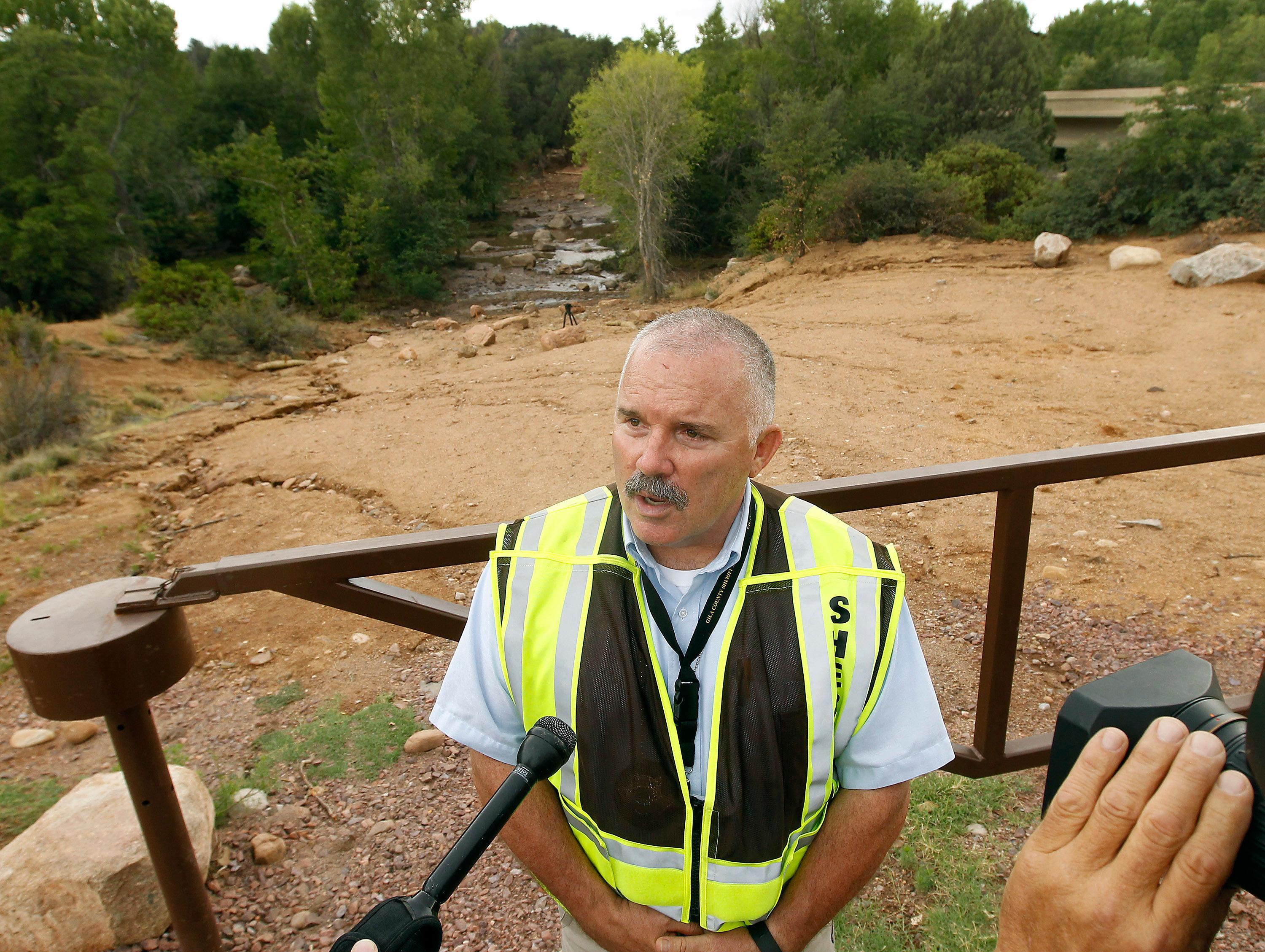 Gila County Sheriff's Office Sgt. David Hornung briefs members of the media during a search and rescue operation for victims of a flash flood along the banks of the East Verde River, Sunday, July 16, 2017, in Payson, Ariz. Search and rescue crews, including 40 people on foot and others in a helicopter, have recovered bodies of children and adults, some as far as two miles down the river after Saturday's flash flooding poured over a popular swimming area inside the Tonto National Forest in central Arizona. (AP Photo/Ralph Freso)