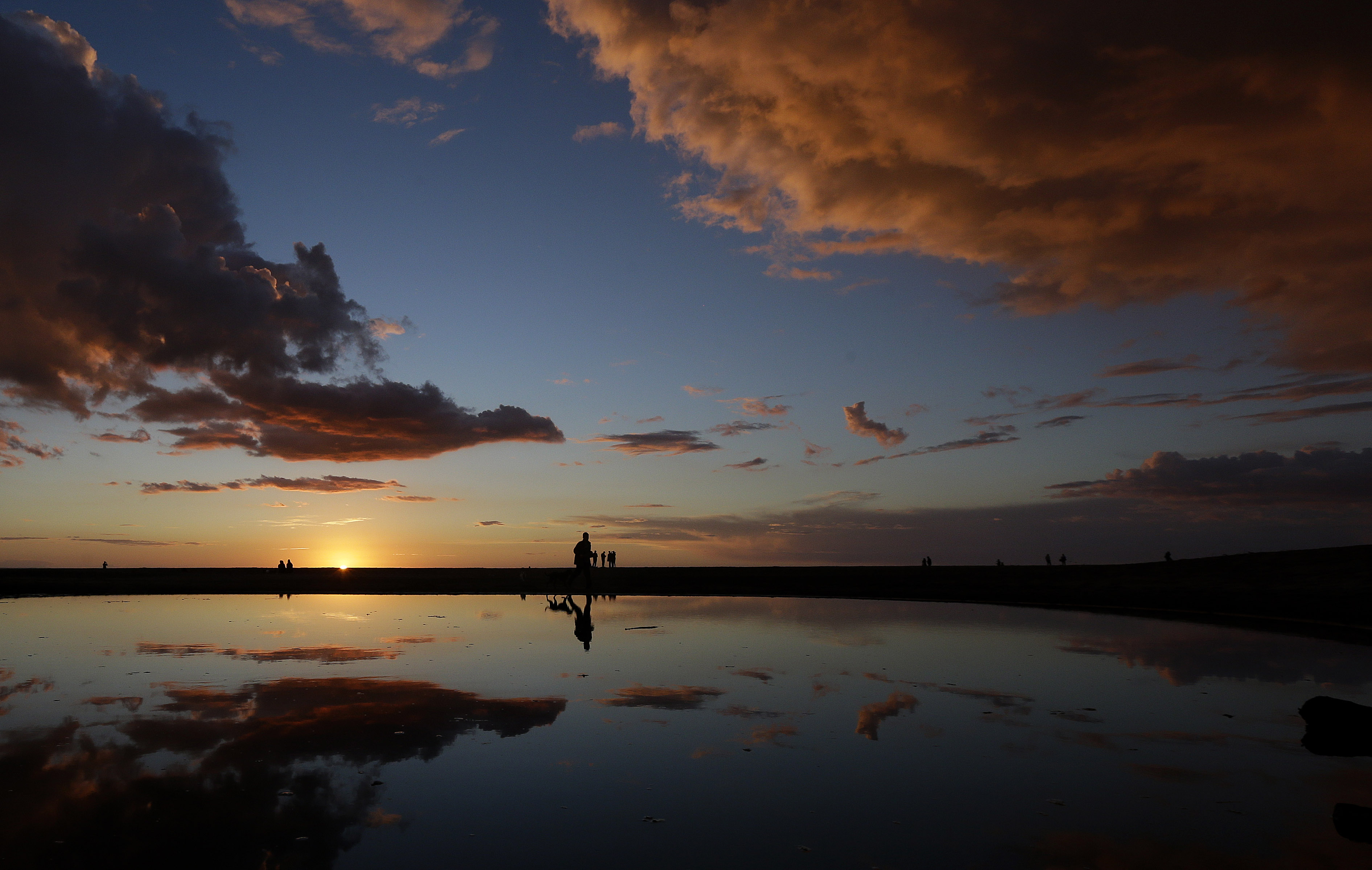 A man walks his dogs past a puddle as the sun sets at Ocean Beach in San Francisco, Saturday, Feb. 28, 2015. (AP Photo/Jeff Chiu)