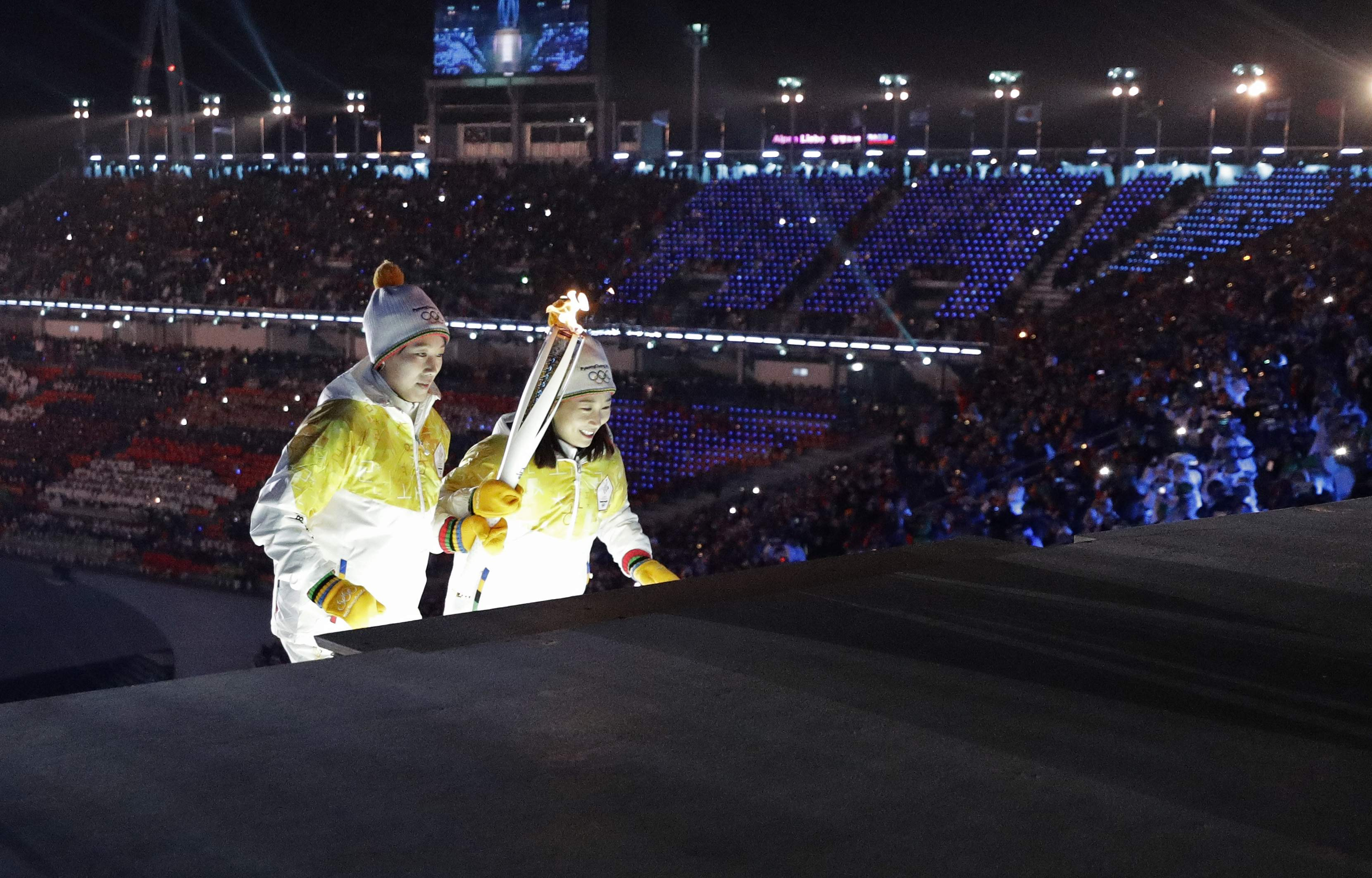Torchbearers climb stairs before lighting the Olympic flame during the opening ceremony of the 2018 Winter Olympics in Pyeongchang, South Korea, Friday, Feb. 9, 2018. (AP Photo/David J. Phillip,Pool)