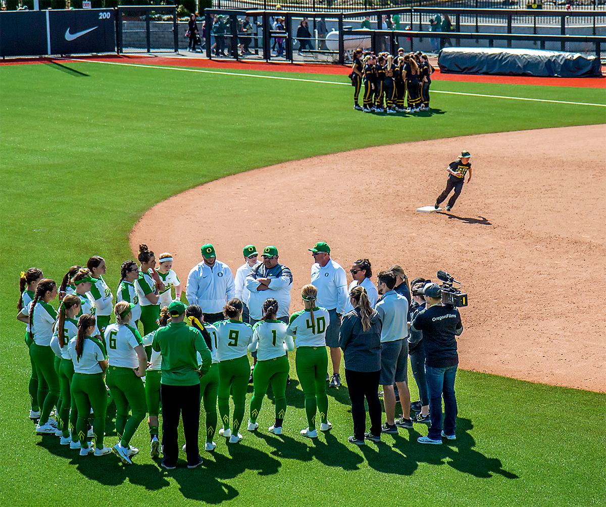 The teams converge together post game as kids run the bases. The Oregon Ducks Softball team took their third win over the Arizona Sun Devils, 1-0, in the final game of the weekends series that saw the game go into an eighth inning before the Duck?s Mia Camuso (#7) scored a hit allowing teammate Haley Cruse (#26) to run into home plate for a point. The Ducks are now 33-0 this season and will next play a double header against Portland State on Tuesday, April 4 at Jane Sanders Stadium. Photo by August Frank, Oregon News Lab