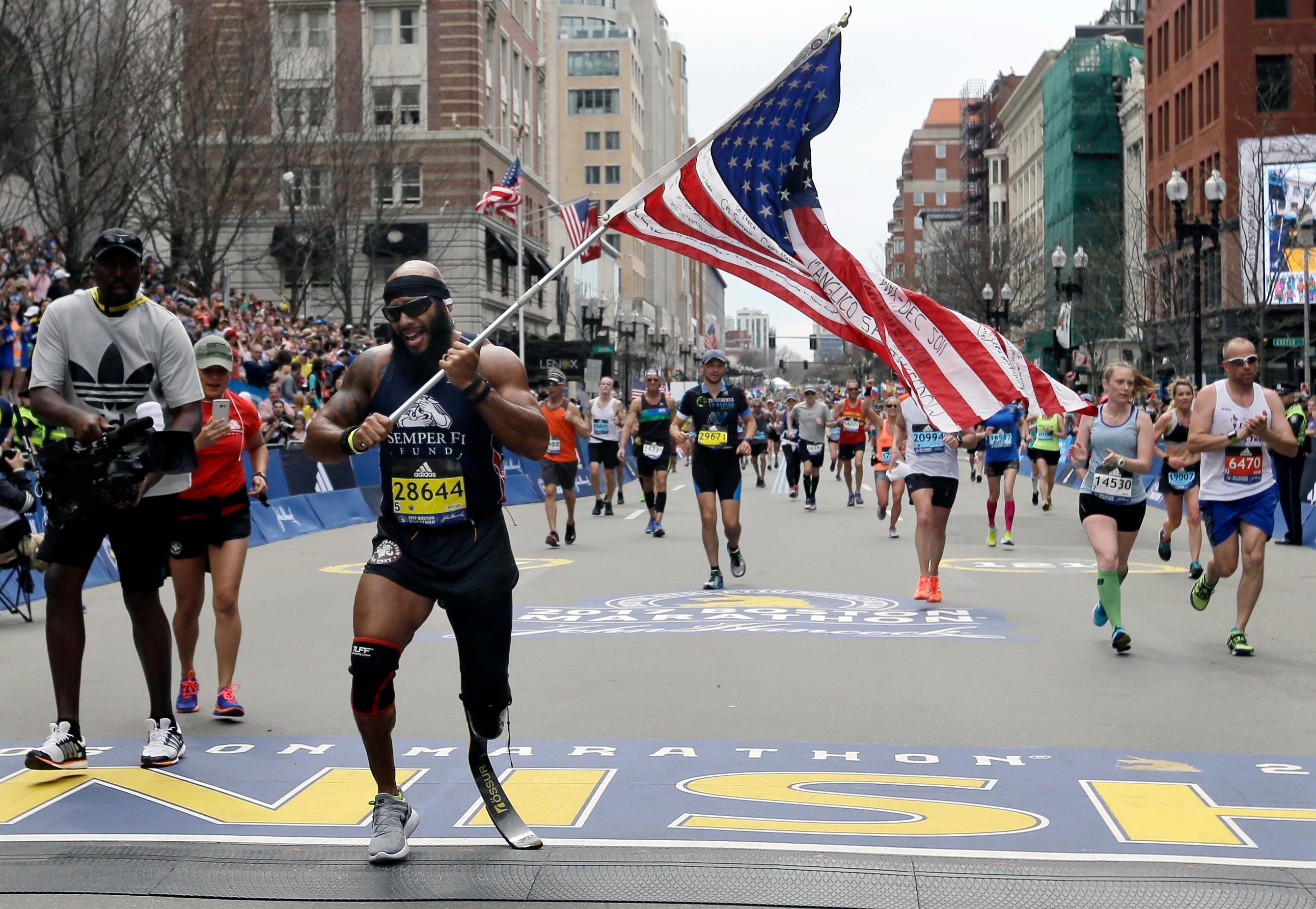 Jose Sanchez, of San Antonio, carries the United States flag across the finish line in the 121st Boston Marathon on Monday, April 17, 2017, in Boston. (AP Photo/Elise Amendola)