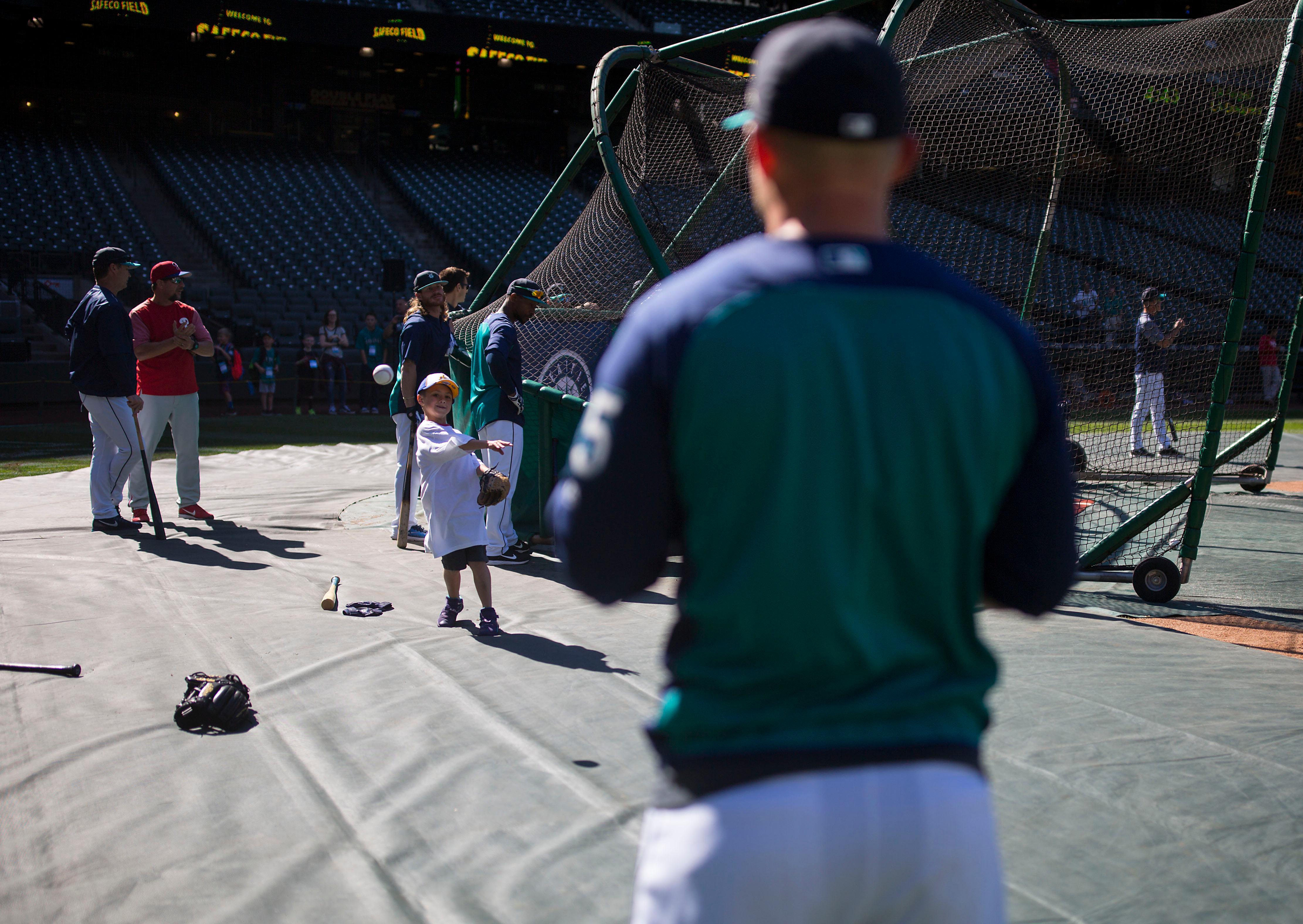 "Seven-year-old kidney cancer survivor Mason Nettleton plays catch with Seattle Mariner Kyle Seager as Nettleton served Seattle as a ""Superhero for a Day"" on Tuesday, June 27, 2017. (Sy Bean/ Seattle Refined)"