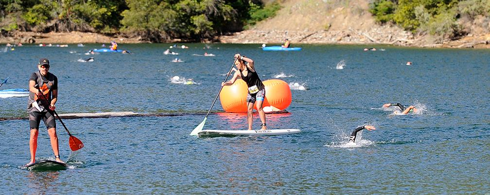 Paddleboard leaders and swimmers make their way on and in Applegate Lake during the Granite Man Triathlon Saturday.