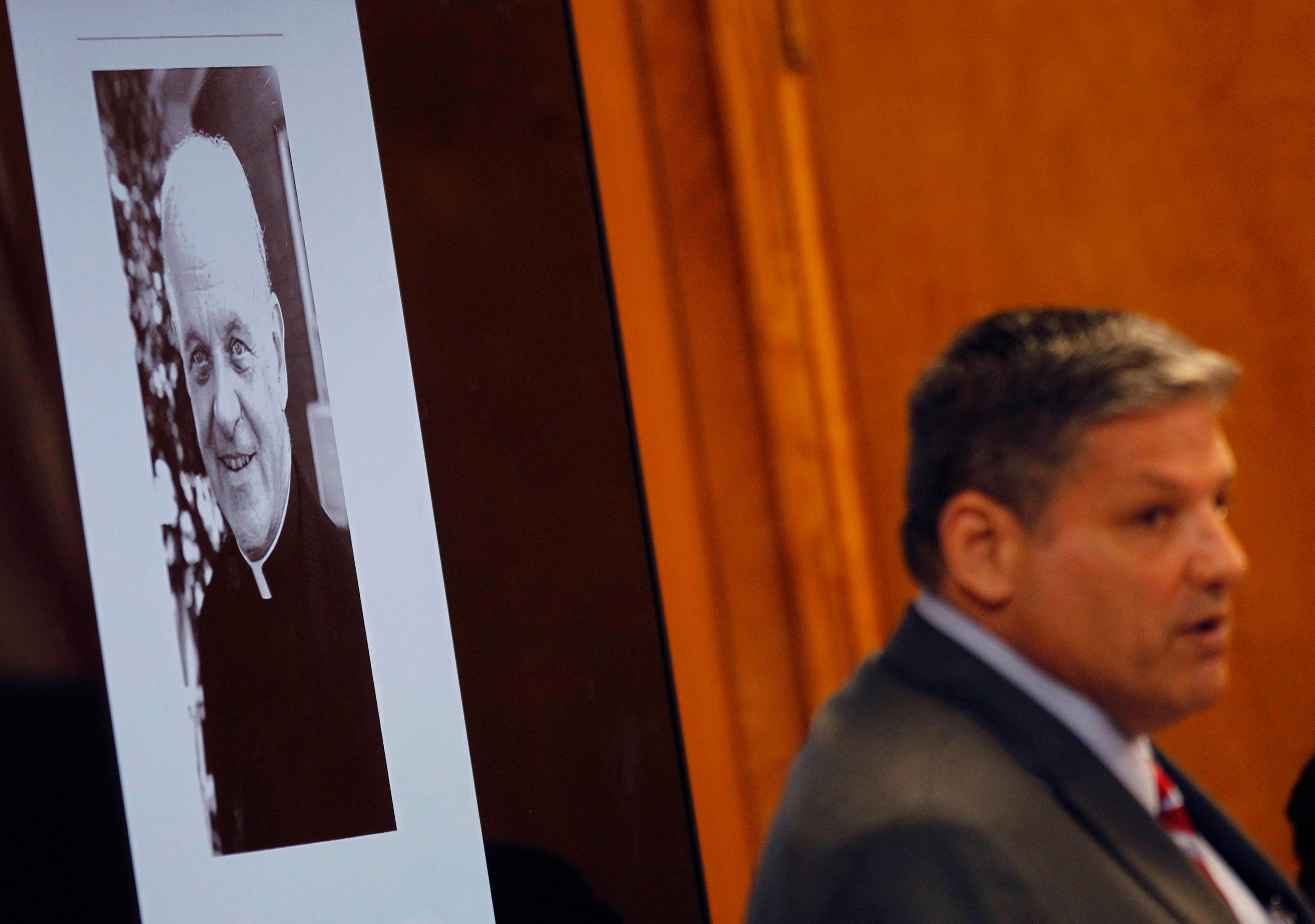 A photograph of Rev. Joseph O'Brien is views behind Hidalgo County Assistant District Attorney Michael Garza during testimony in John Bernard Feit's trial for the 1960 murder of Irene Garza Tuesday, December 5, 2017, at the Hidalgo County Courthouse in Edinburg. O'Brien spoke out to several people that Feit admitted to him that he committed the Garza's murder in 1960, O'Brien died in 2005. (Nathan Lambrecht/The Monitor/Pool)