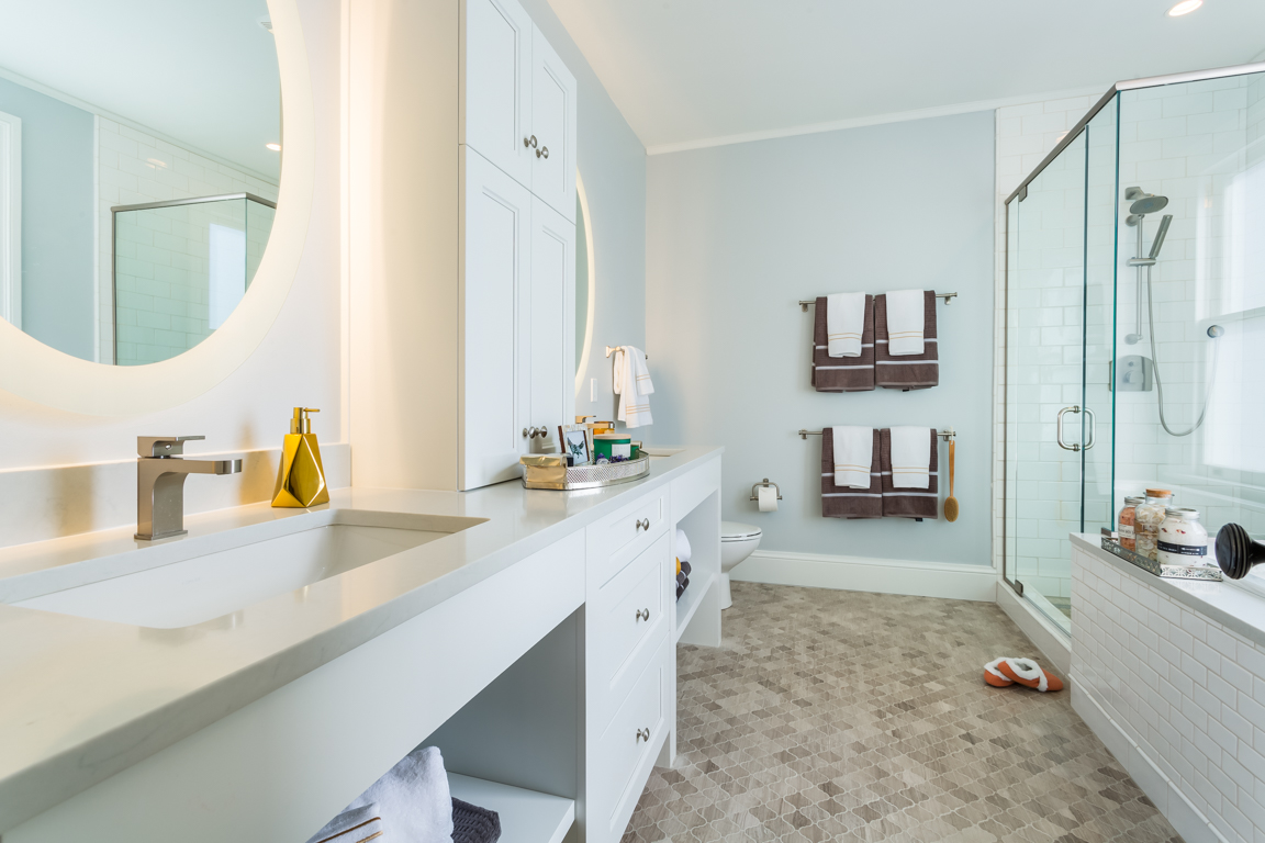 This updated master bathroom features a glass walk-in glass shower, soaking tub, and a double sink vanity, custom lighting and heated marble floors.