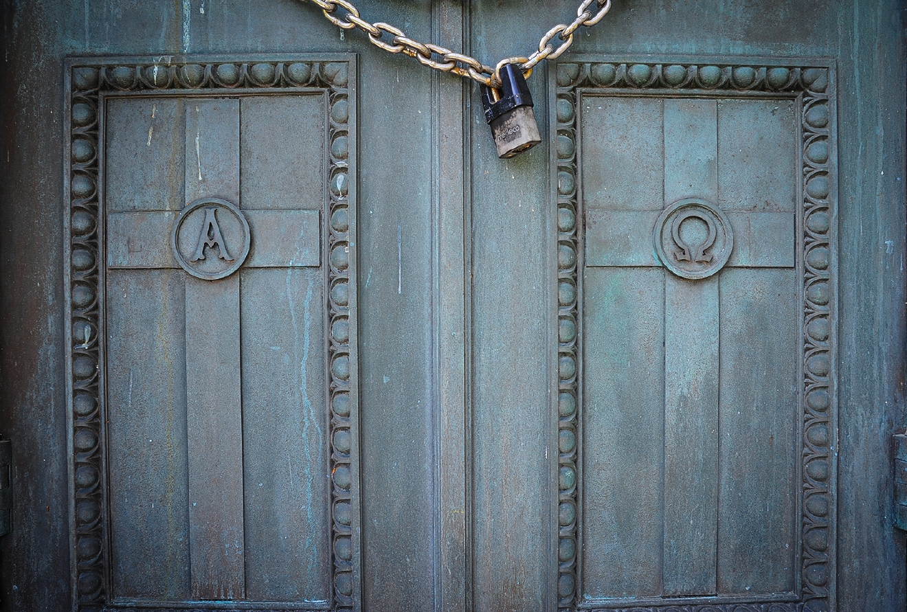 Alpha and omega symbols on the doors of a family mausoleum. / Image: Melissa Doss Sliney