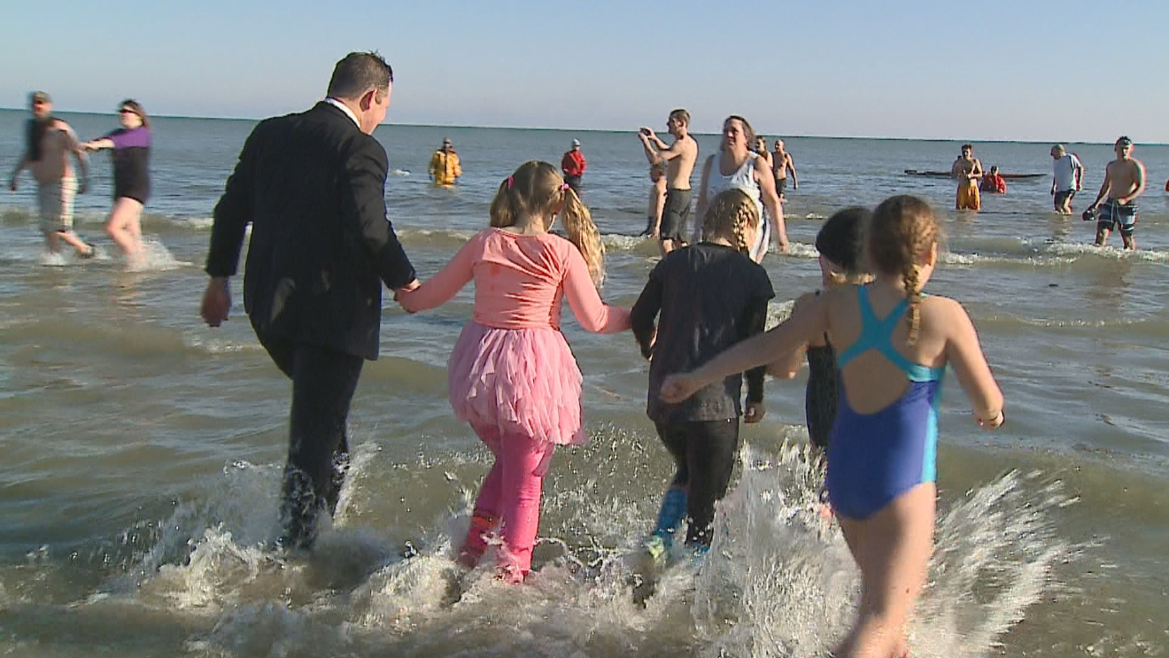 A family plunges into Lake Michigan. (WLUK/Eric Peterson)