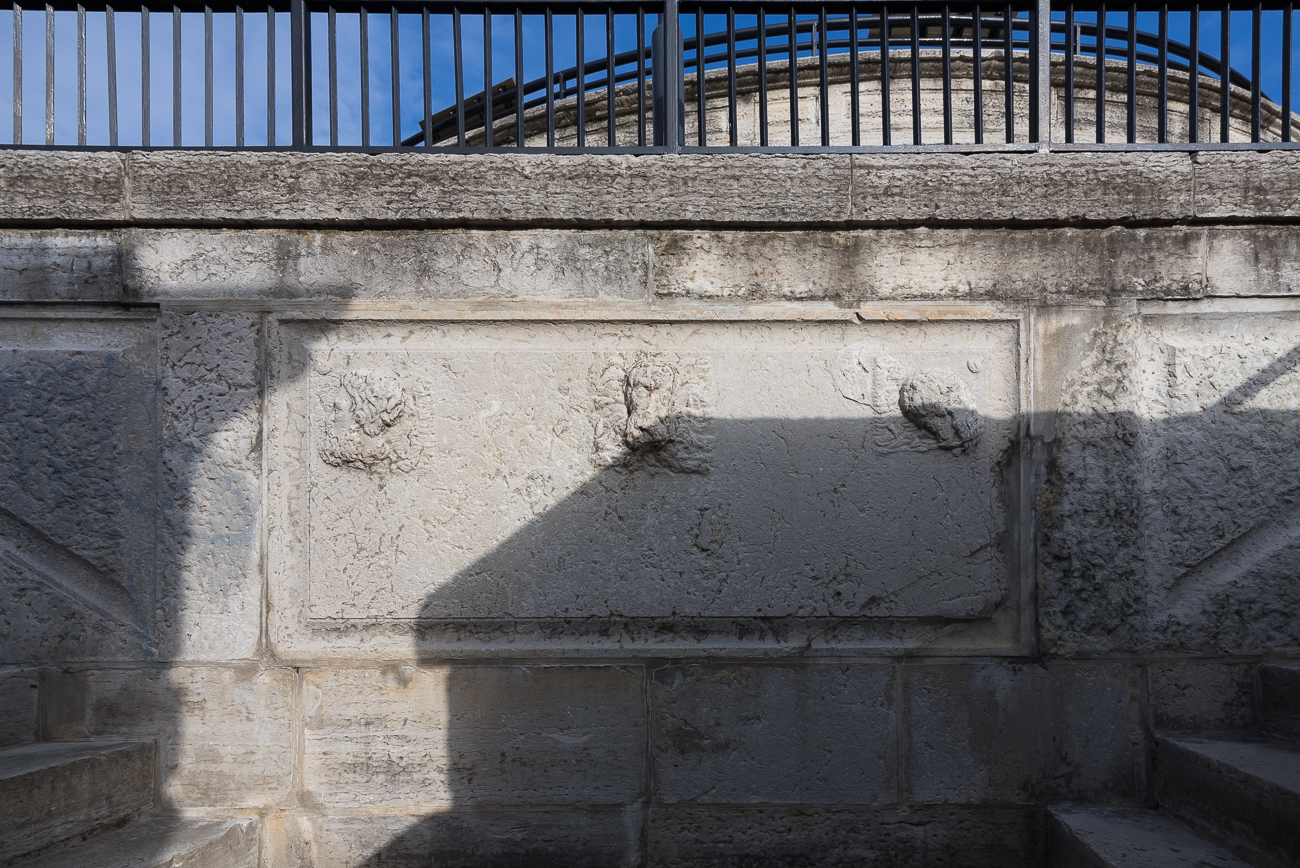 The weathered remains of three Roman heads can be barely made out as the stairs divide into two sets that lead up to a landing above it. / Image: Phil Armstrong, Cincinnati Refined // Published: 4.13.18