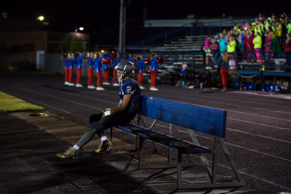Springfield quarterback Bryson Breese (#2) sits alone on the bench as the defense takes the field. The Churchill Lancers defeated the Springfield Millers 56-7 in a cold game Friday night. Friday night's win extended Churchill's season to 7-0. Photo by Dillon Vibes