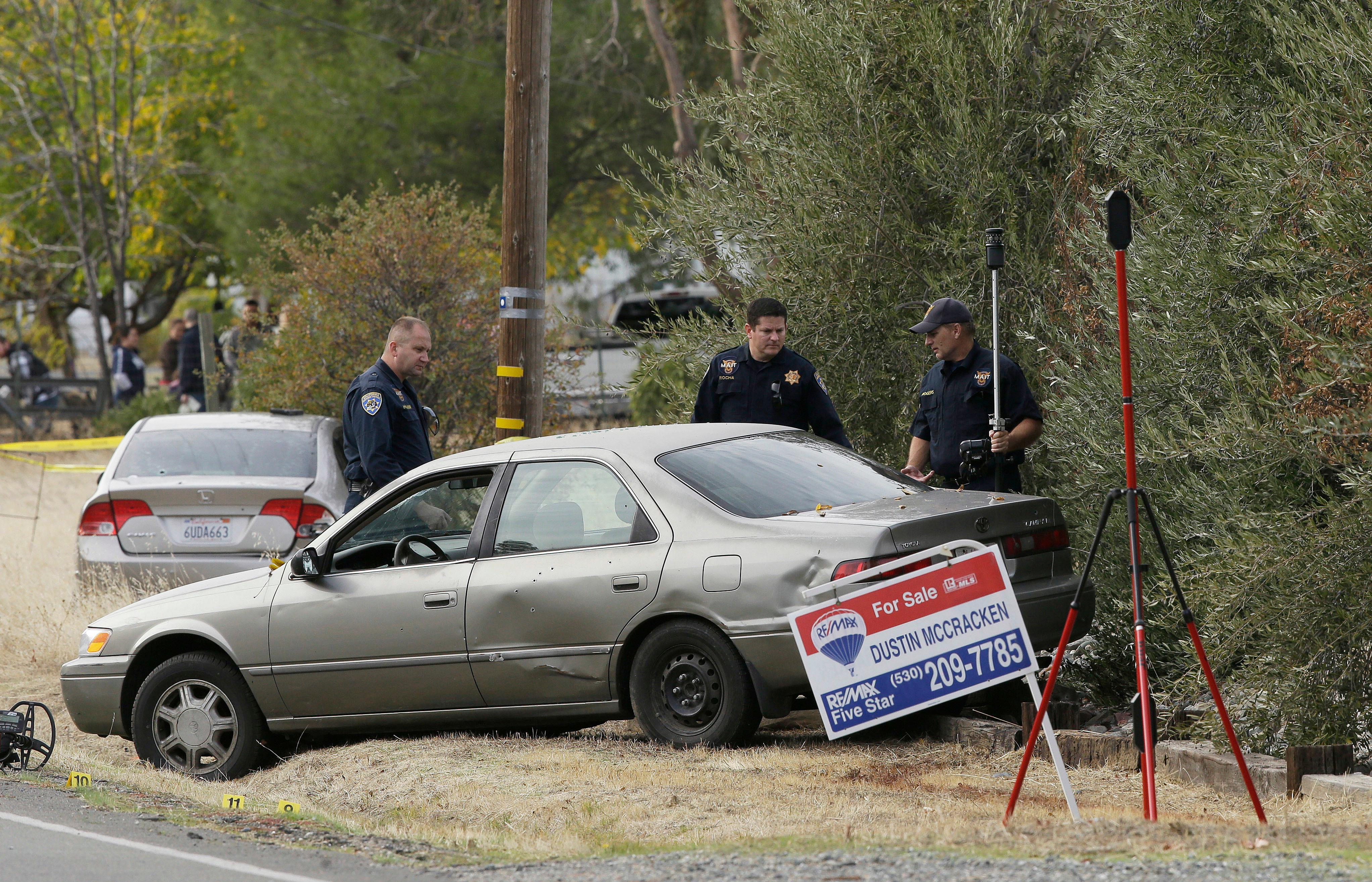 California Highway Patrol Officers inspect one of the vehicles involved when a gunman went on a shooting rampage at the Rancho Tehama Reserve, near Corning, Calif., Tuesday, Nov. 14, 2017. Law enforcement says that five people, including the shooter were killed, and several people were injured during the shooting spree that occurred at multiple locations. (AP Photo/Rich Pedroncelli)