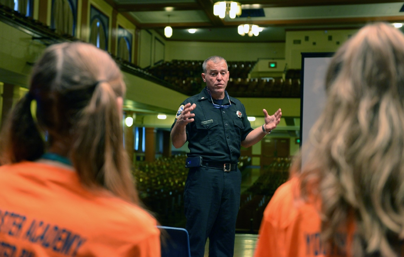 A representative from Portland Fire gives a presentation during the Portland Public Schools' Youth Disaster Academy at Benson High School, prior to the Great Oregon ShakeOut drill on Oct. 20. Portland Public Schools, in partnership with the Portland Bureau of Emergency Management, Portland Fire & Rescue and Oregon Office of Emergency Management (OEM), engaged approximately 100 Benson High School students in emergency preparedness skills training including hands-only CPR, an introduction to search and rescue/medical triage, small fire suppression, radio communications and an overview of local hazards. Students also received copies of a new comic book about tsunamis, an OEM collaboration with Dark Horse Comics that can be viewed here: http://bit.ly/2dWuS0G. (Oregon Office of Emergency Management photo by Cory E. Grogan)