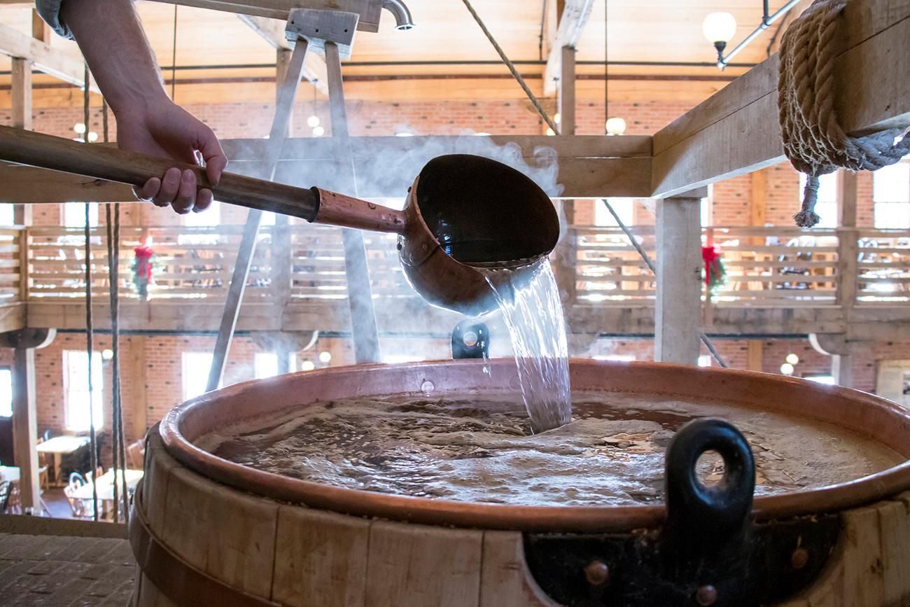 Each day water is drawn to begin a new batch of beer. A charcoal and wood fire are built beneath the kettle to bring the water to near boiling. This water is then hand-ladled into the wort, the sugary water. / Image: Allison McAdams // Published: 1.16.18<p></p>