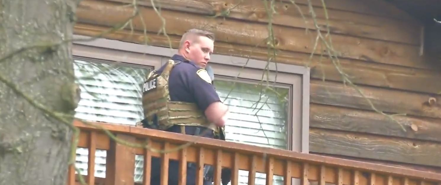 An officer stands ready at the scene of a standoff at Hunters Ridge Road in Charleston. (WCHS/WVAH)