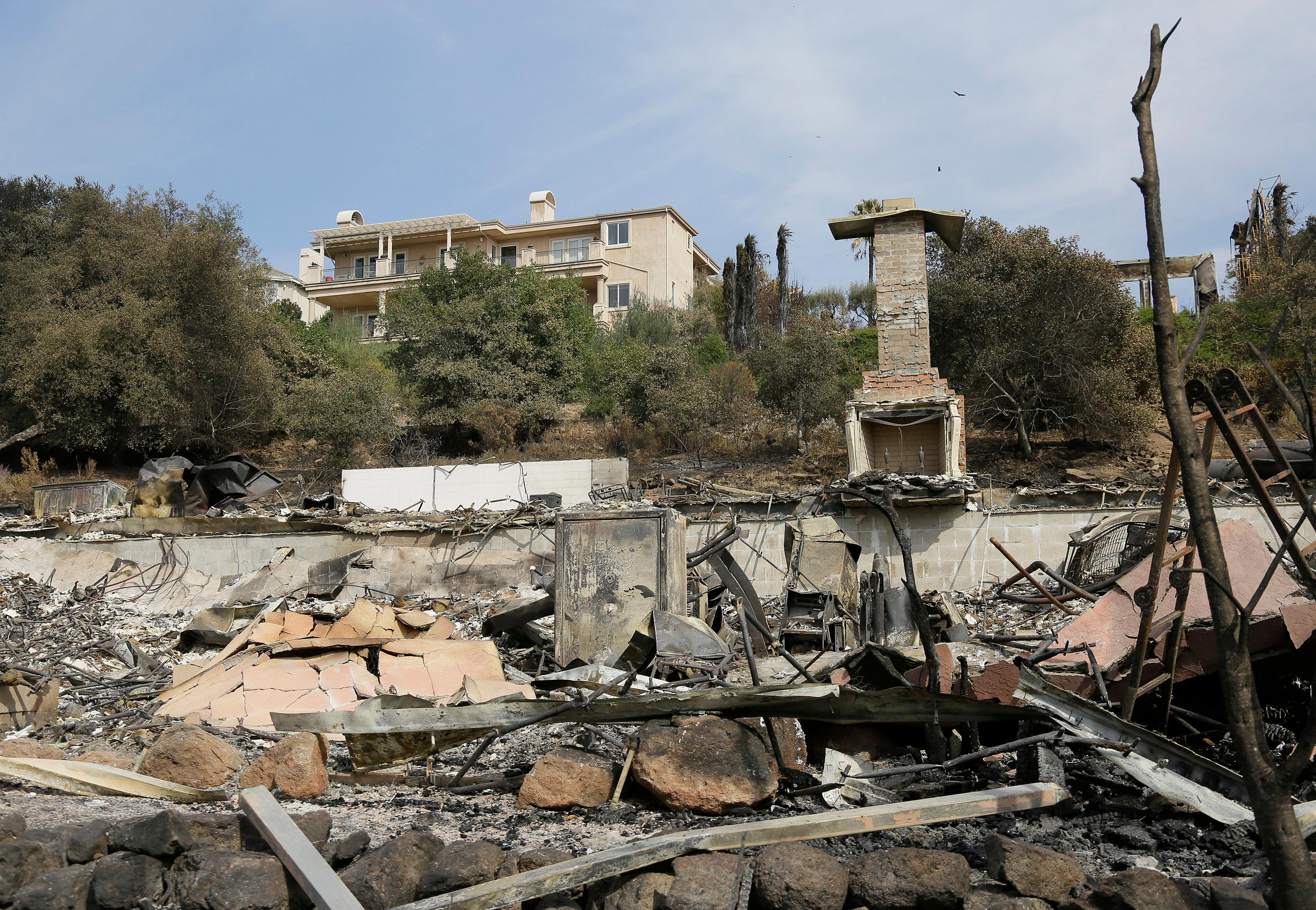 A house stands intact above one that was destroyed by wildfire near Atlas Peak Road Monday, Oct. 16, 2017, in Napa, Calif. State and local officials say they are trying to get people back into their homes, but they cautioned that it could take days and even weeks for neighborhoods hard hit by Northern California wildfires. (AP Photo/Eric Risberg)