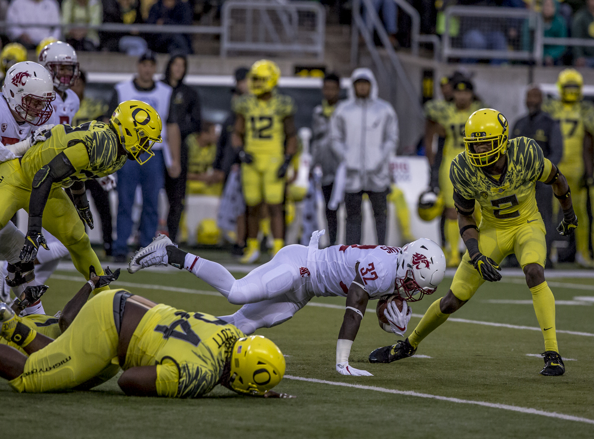 Washington State running back James Williams (#32) dives forward with the ball. The Oregon Ducks trail the Washington State Cougars 10 to 13 at the end of the first half. Photo by Ben Lonergan, Oregon News Lab
