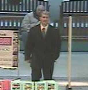 Store surveillance captured a white male walking into the store dressed in a dark suit and blue tie. (Image: Dalton PD)<p></p>