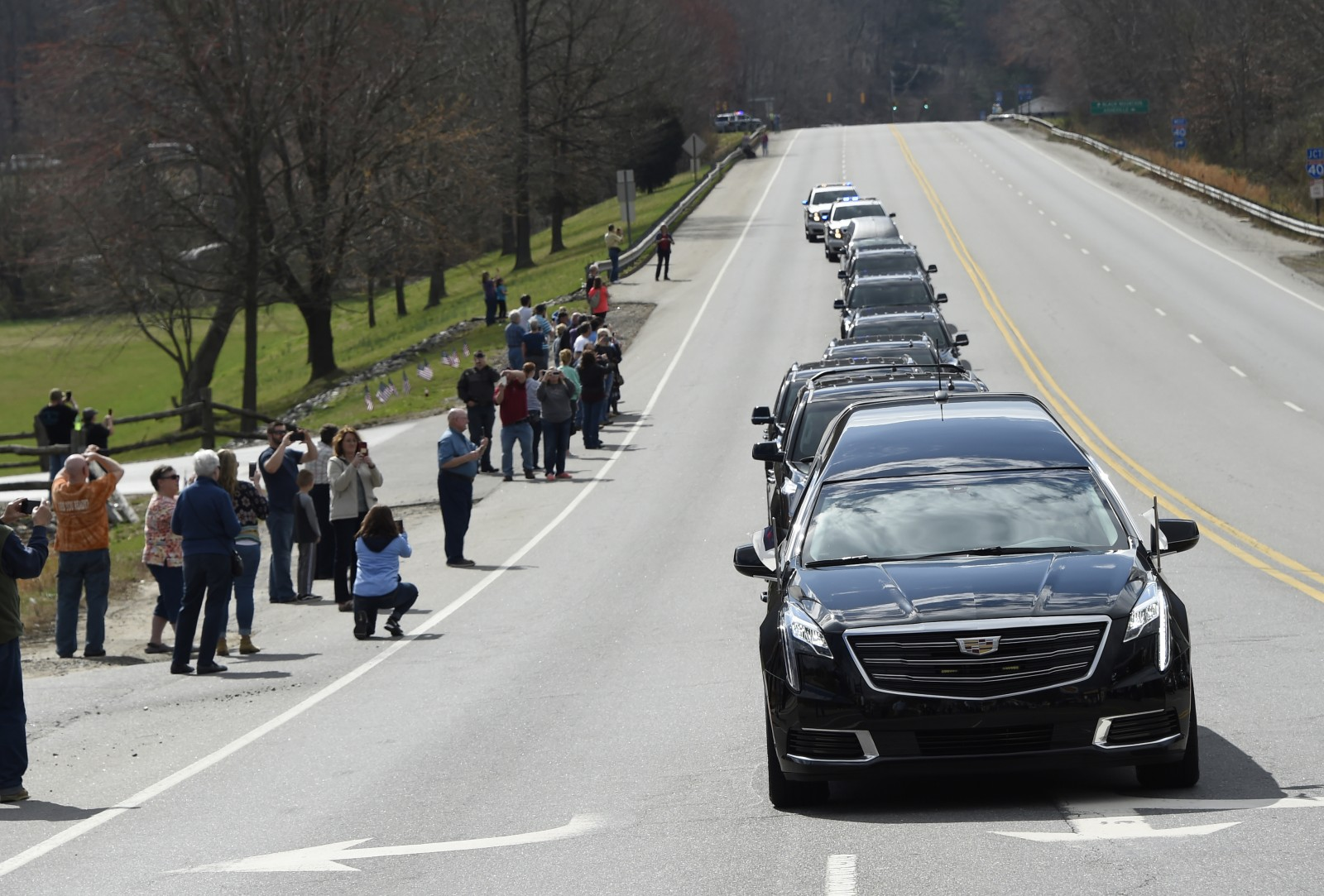 People watch as the hearse carrying the body of Billy Graham leaves Asheville, N.C., Saturday, Feb. 24, 2018. Graham's body was brought to his hometown of Charlotte on Saturday, Feb. 24, as part of a procession expected to draw crowds of well-wishers. (Kathy Kmonicek/pool photo)