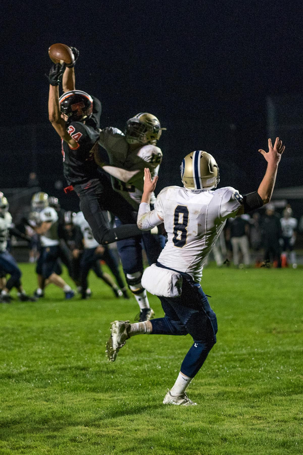 Thurston Colt Tyson Haas (#34) attempts to complete a reception while being pressured by Marist Spartans Mitchell Hopkins (#12) and Jace Krier (#8). The Thurston Colts defeated the Marist Catholic Spartans 50 – 14 to seal second place in their conference at Thurston High School on Friday, October 13. Photo by Kit MacAvoy, Oregon News Lab