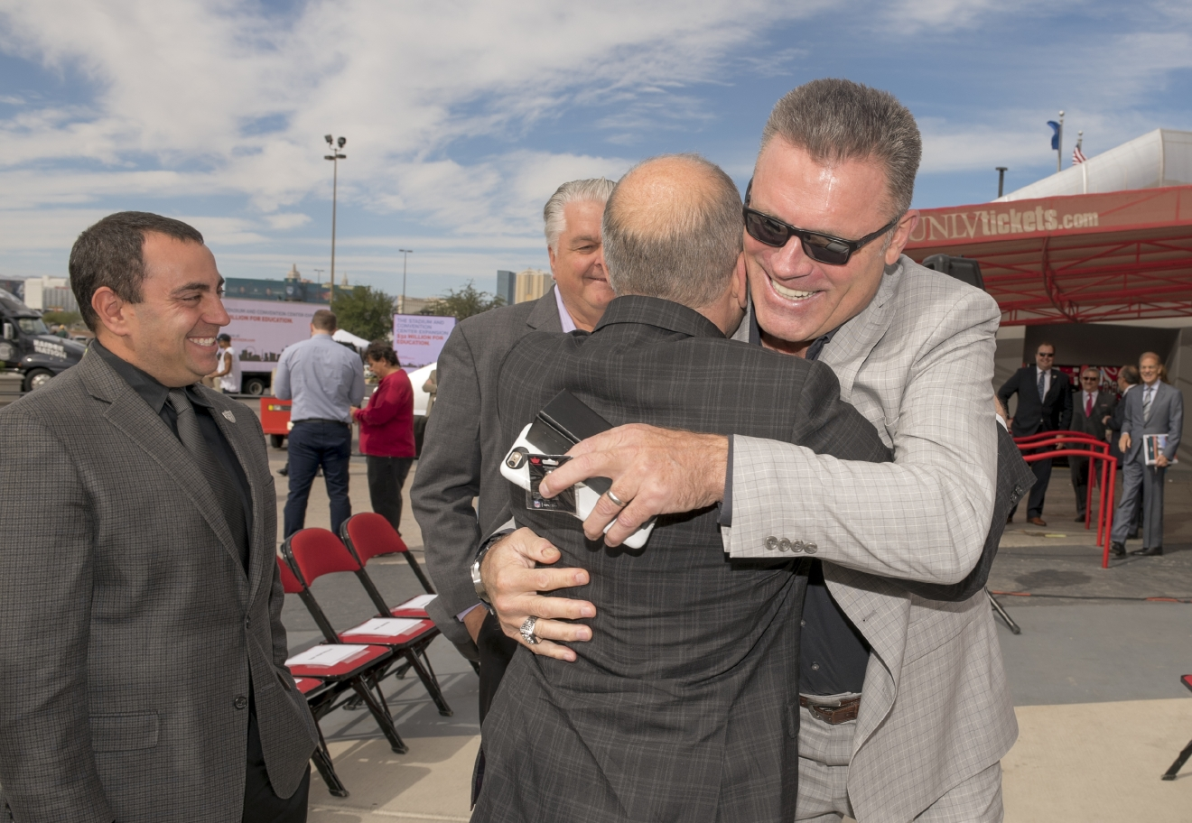 Former Oakland Raider Howie Long, right, embraces Oakland Raiders President Marc Badain as they meet before a coalition of gaming and community leaders called Win Win Nevada gathers to announce the support for immediate legislative approval of the Las Vegas Convention Center expansion and a new football stadium, both unanimously approved by the Governor's Southern Nevada Tourism Infrastructure Committee, at the Thomas & Mack arena at UNLV on Monday, Oct. 3. 2016. (Mark Damon/Las Vegas News Bureau)
