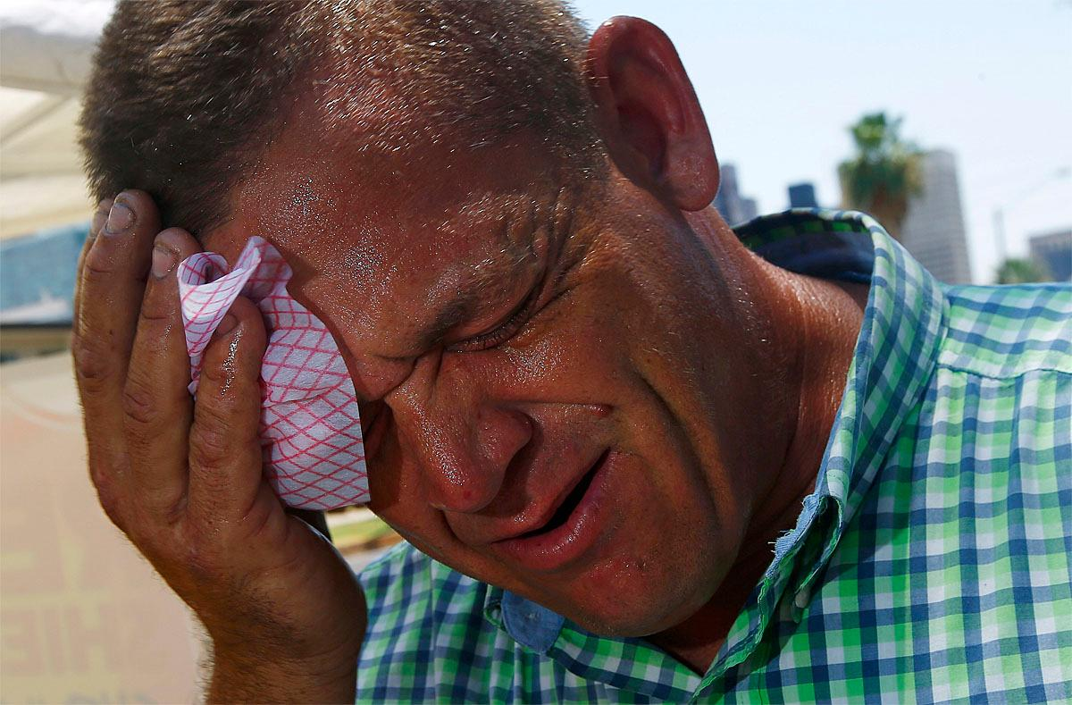 Steve Smith wipes sweat from his face as temperatures climb to near-record highs in Phoenix on Monday, June 19, 2017. (AP Photo/Ross D. Franklin)