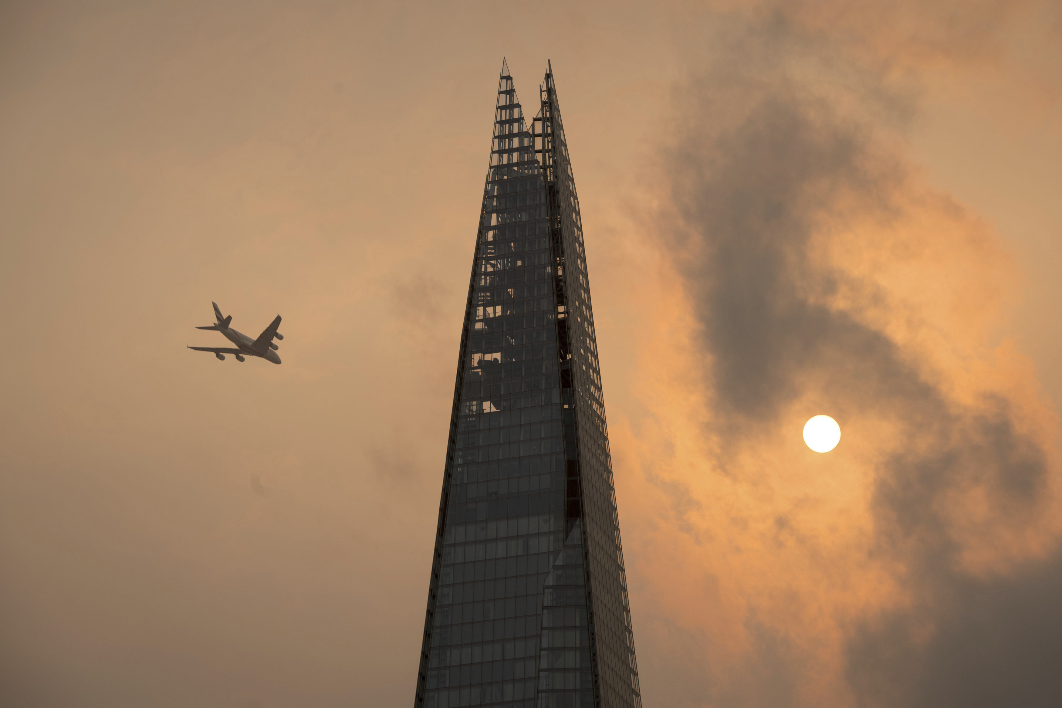A plane flies past the Shard in central London, as the sky takes on an unusual orange colour caused by Hurricane Ophelia Monday Oct. 16, 2017. The unusual occurrence was due to the remnants of the hurricane dragging in tropical air and dust from the Sahara.  (Dominic Lipinski/PA via AP)