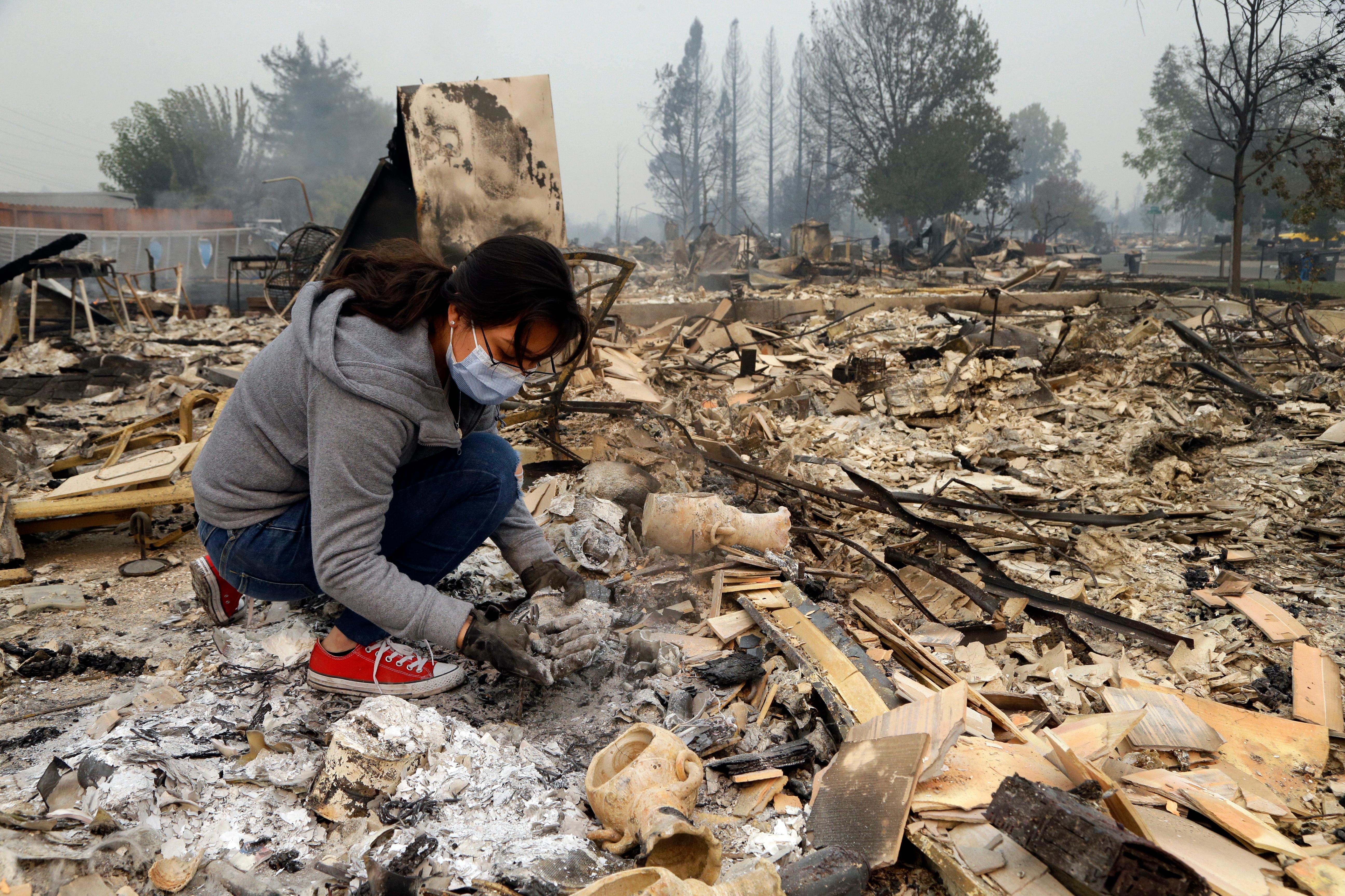 Leslie Garnica searches for belongings in the ashes of her home that was destroyed by fire in the Coffey Park area of Santa Rosa, Calif., on Tuesday, Oct. 10, 2017. An onslaught of wildfires across a wide swath of Northern California broke out almost simultaneously then grew exponentially, swallowing up properties from wineries to trailer parks and tearing through both tiny rural towns and urban subdivisions. (AP Photo/Ben Margot)
