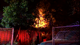 Firefighters struggle to put out shed fire due to heavy brush