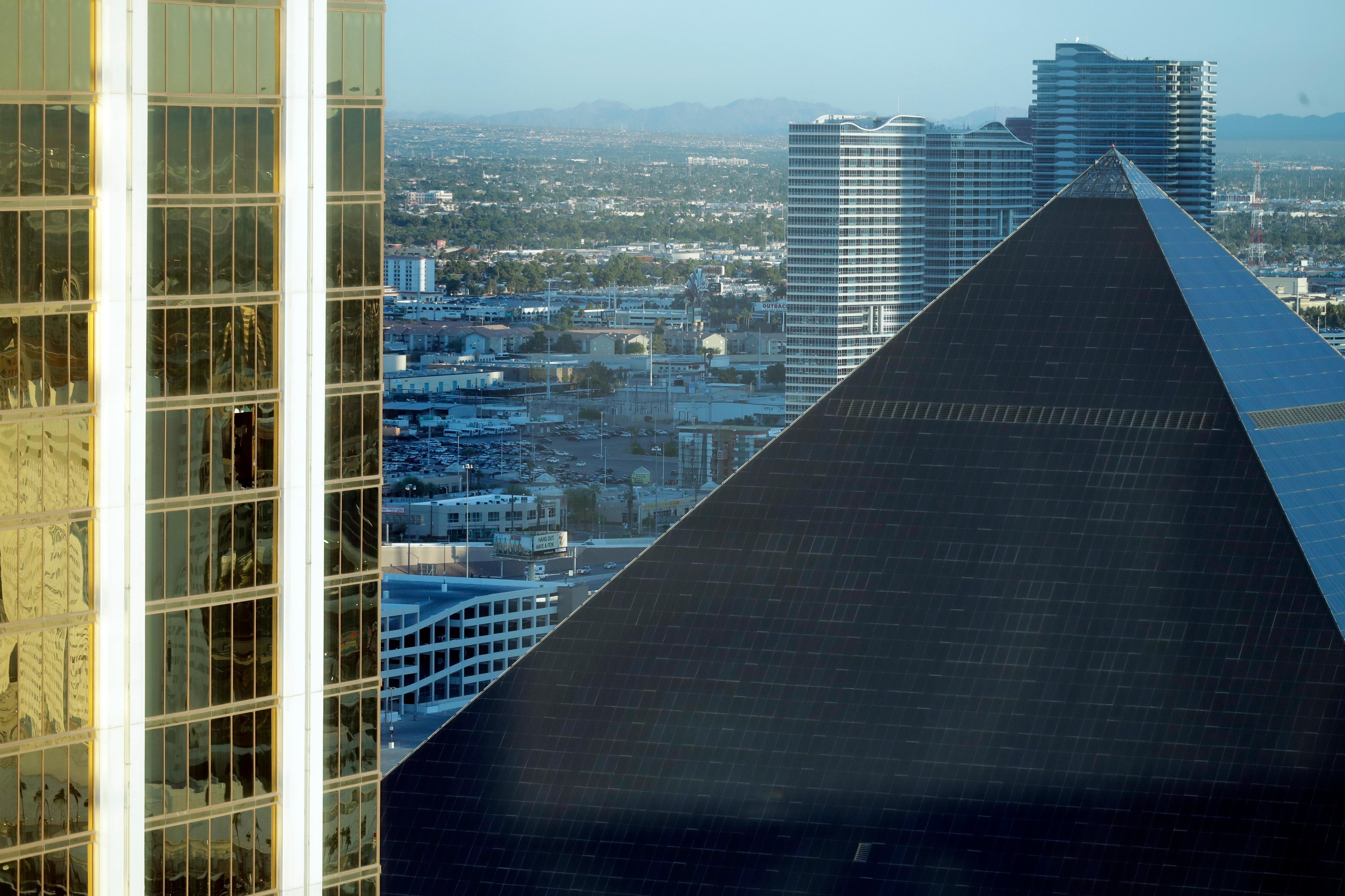 The Mandalay Bay Resort and Casino, at left, with a broken window, stands next to the Luxor in Las Vegas, Tuesday, Oct. 3, 2017. Authorities said Stephen Craig Paddock broke windows on a high floor of the Mandalay Bay and began firing with a cache of weapons, killing dozens and injuring hundreds at a music festival at the grounds. (AP Photo/Marcio Jose Sanchez)