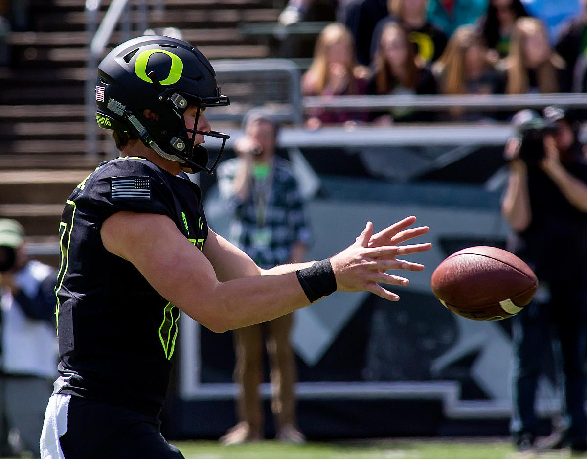 Oregon quarterback Braxton Burmeister (#17) recieves the snap. University of Oregon Ducks football fans gathered for the 2017 Spring Game at Autzen Stadium. The Spring Game served as the first exhibition of Coach Willie Taggart's newly assembled coaching staff. Cost of admission was three cans of non-perishable food to benefit Food for Lane County. Photo by Ben Lonergan, Oregon News Lab