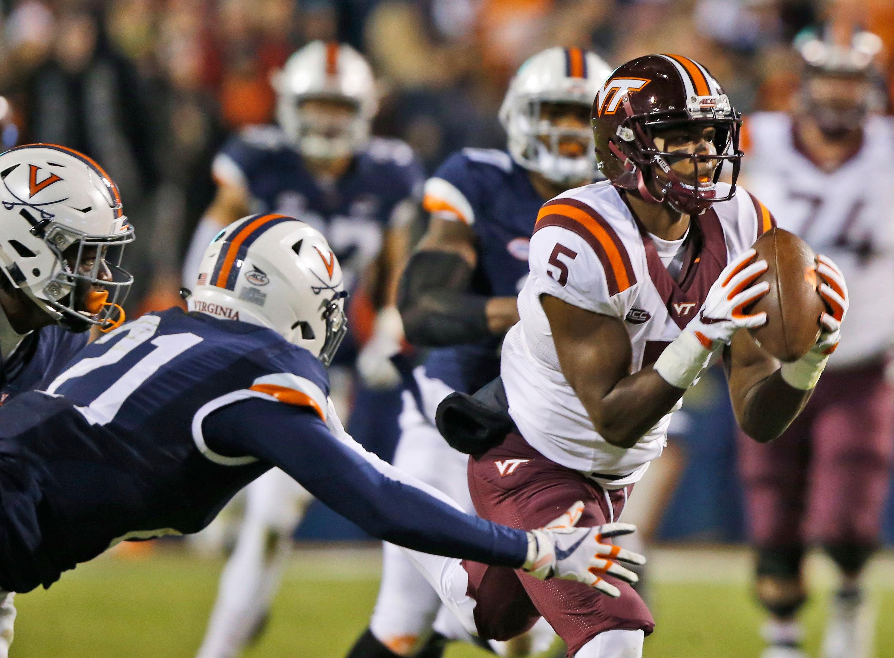 Virginia Tech wide receiver Cam Phillips (5) hauls in a pass in front of Virginia safety Juan Thornhill (21) during the first half of an NCAA college football game in Charlottesville, Va., Friday, Nov. 24, 2017. (AP Photo/Steve Helber)